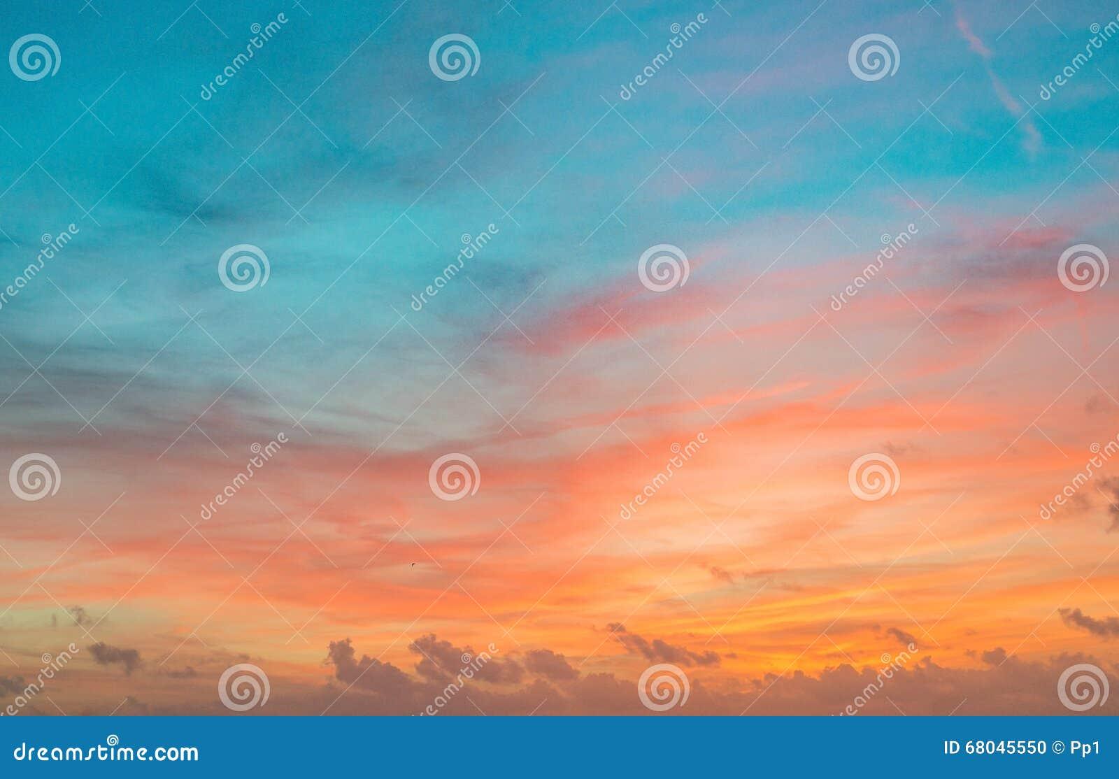 Небо захода солнца в красном и голубом цвете с тонкими облаками
