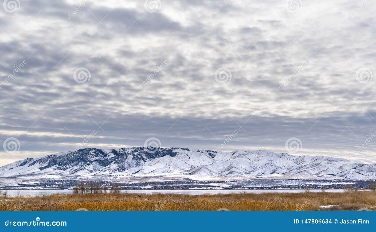 Небо ясной панорамы драматическое заполненное с cottony облаками над сценарным ландшафтом в зиме