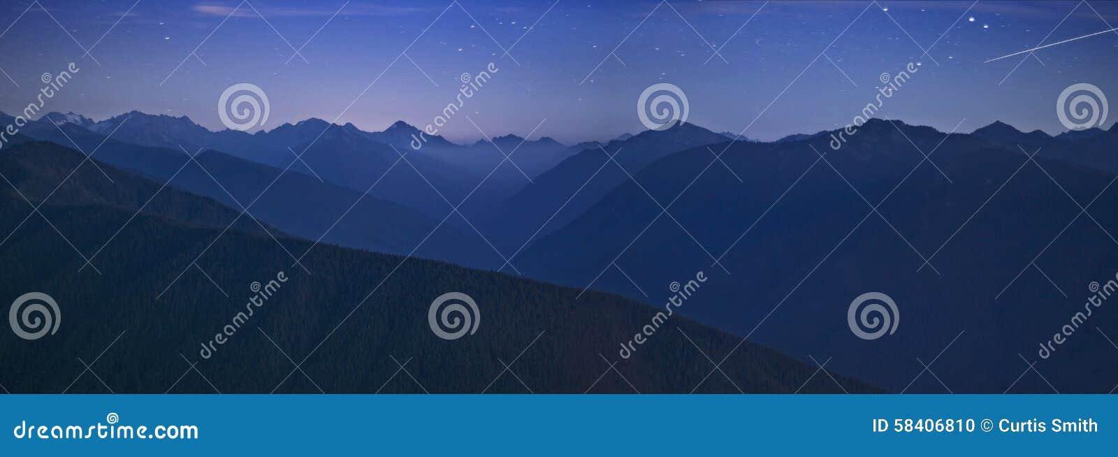 Небо nighttime и олимпийская горная цепь с звездой стрельбы