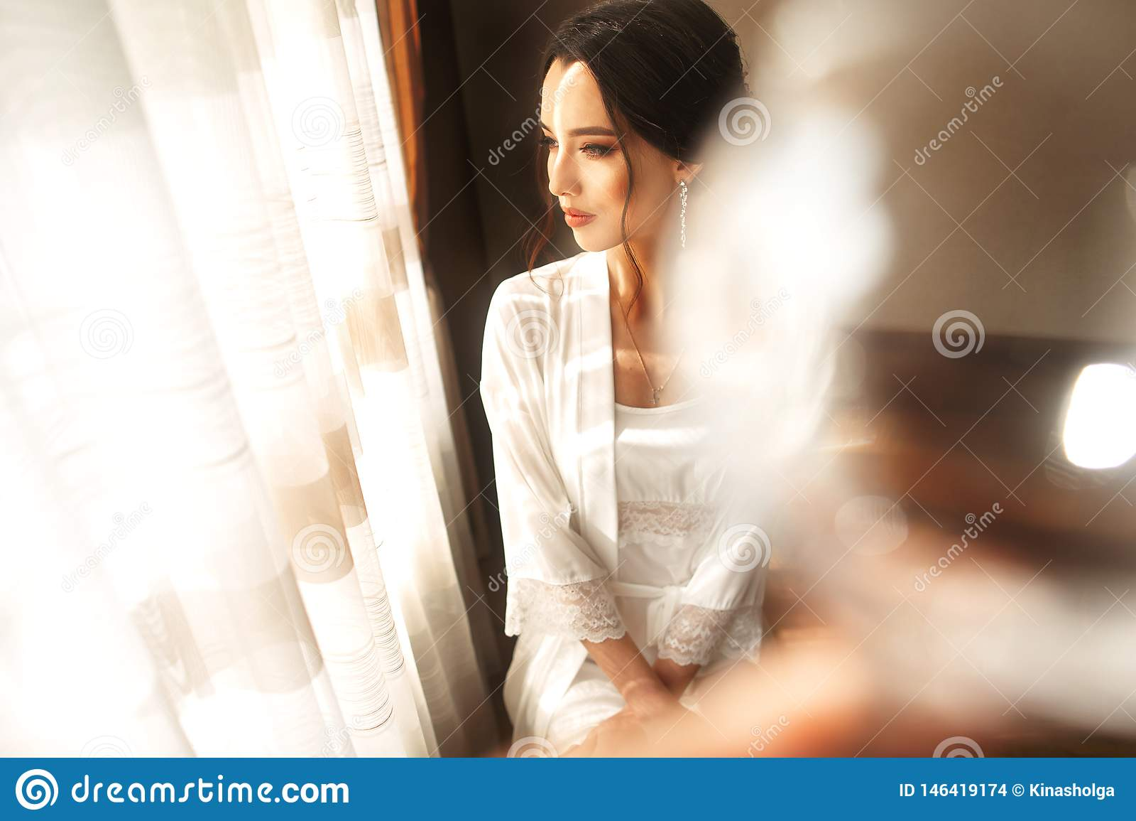 Невеста в красивом платье сидя на стуле внутри помещения в белом интерьере студии как дома Ультрамодная съемка стиля свадьбы
