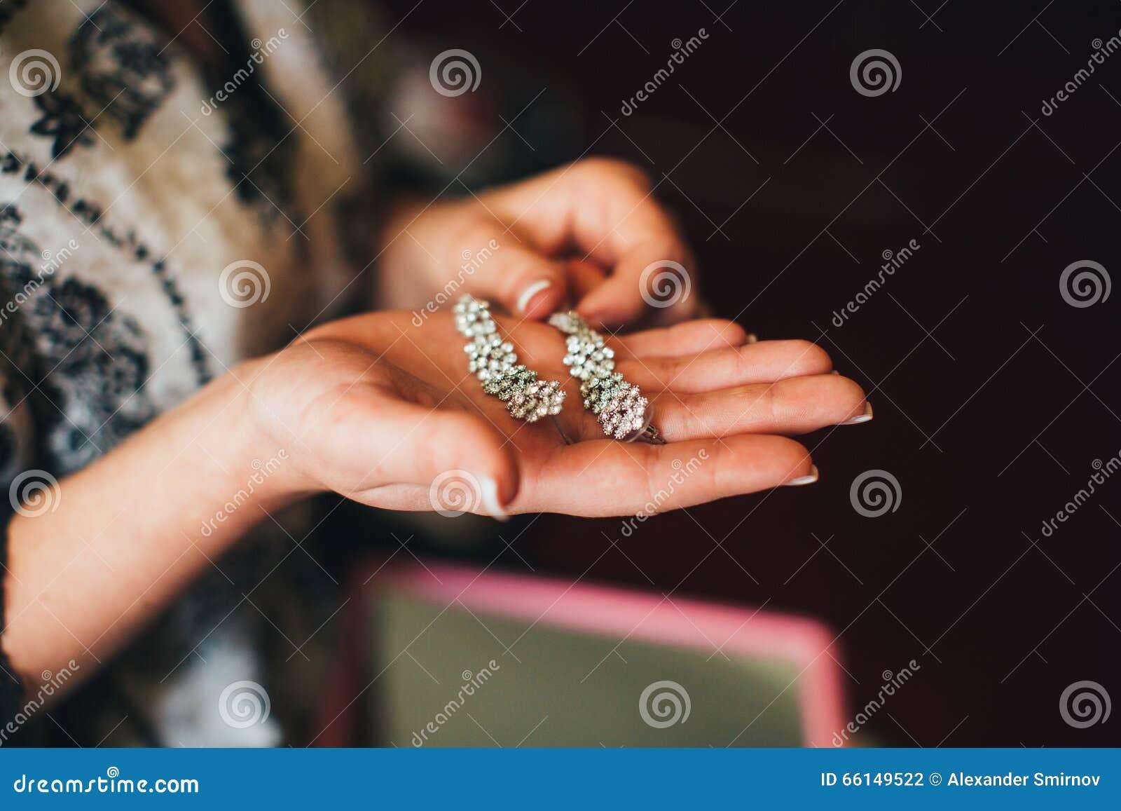 Невеста держит серьги