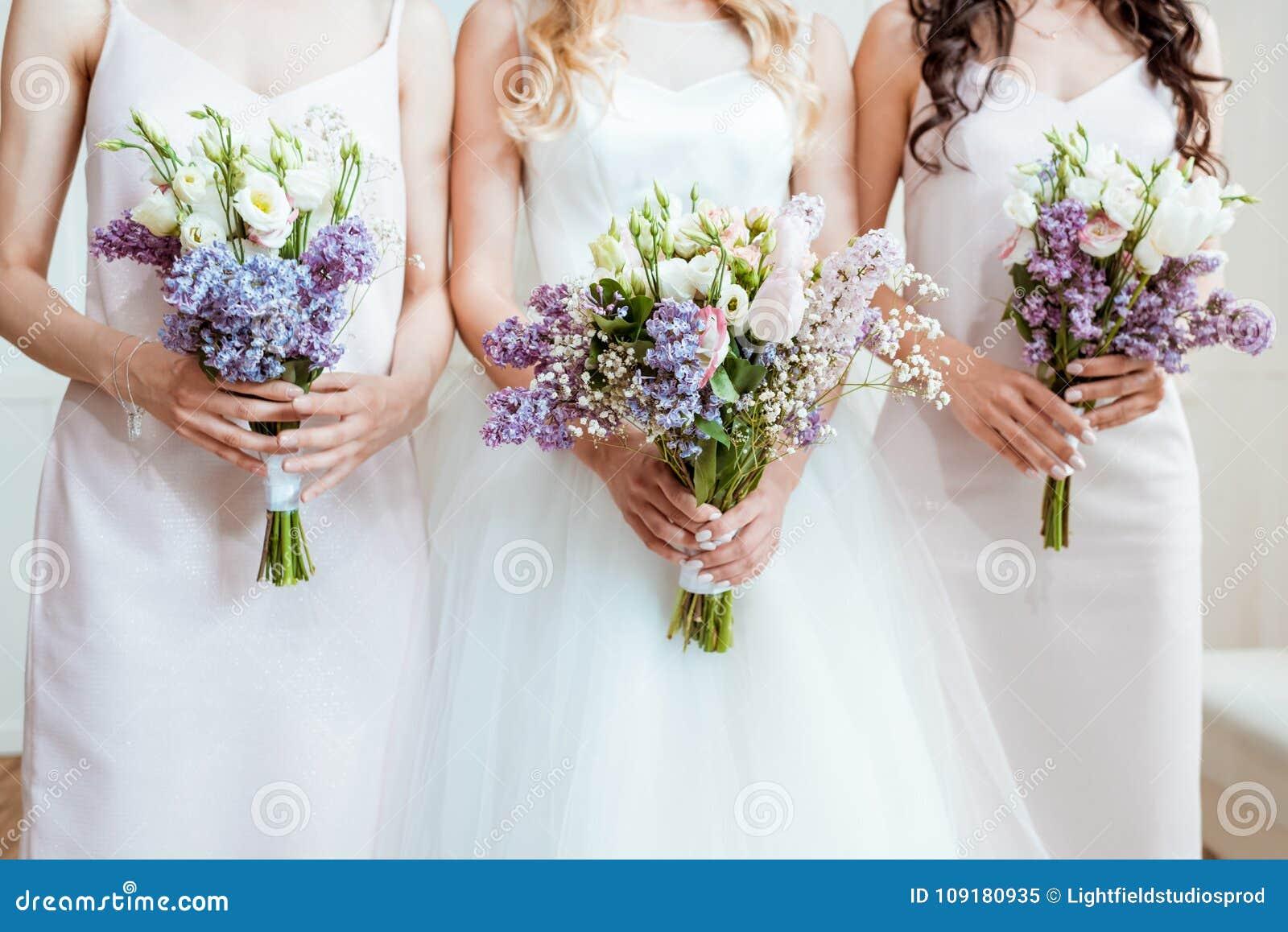 Невеста при bridesmaids держа букеты