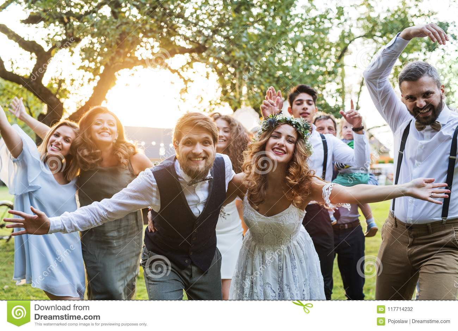 Невеста, groom, гости представляя для фото на приеме по случаю бракосочетания снаружи в задворк