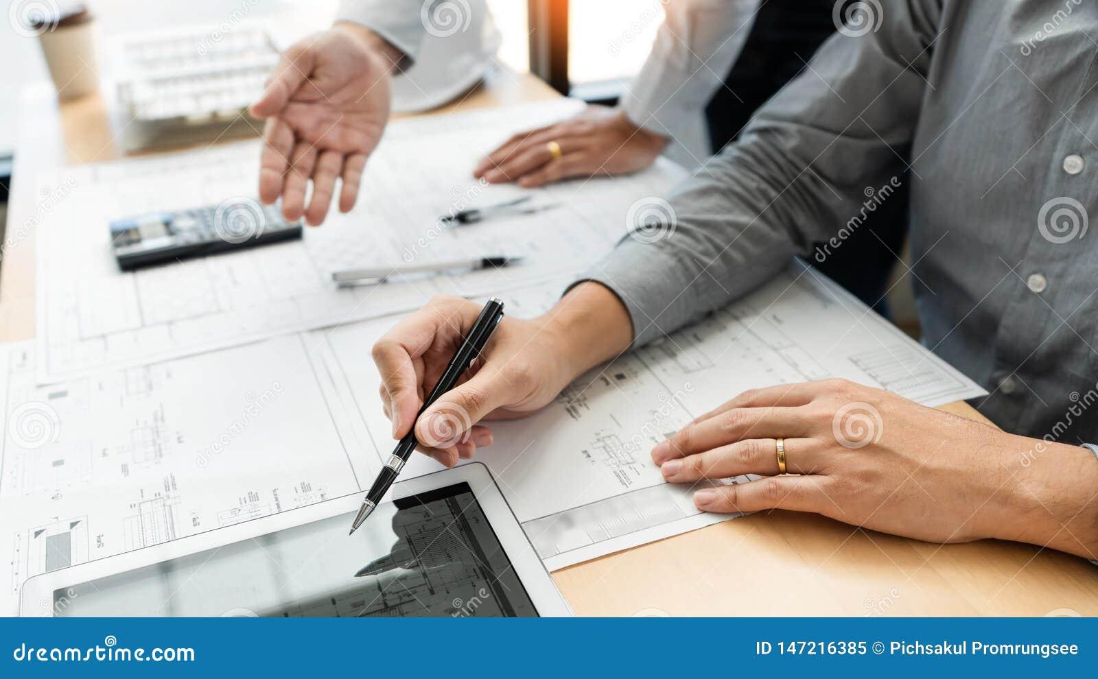 Недвижимая концепция, 2 инженер и архитектор обсуждая работу данных по светокопий и цифровой планшет на здании конструкции