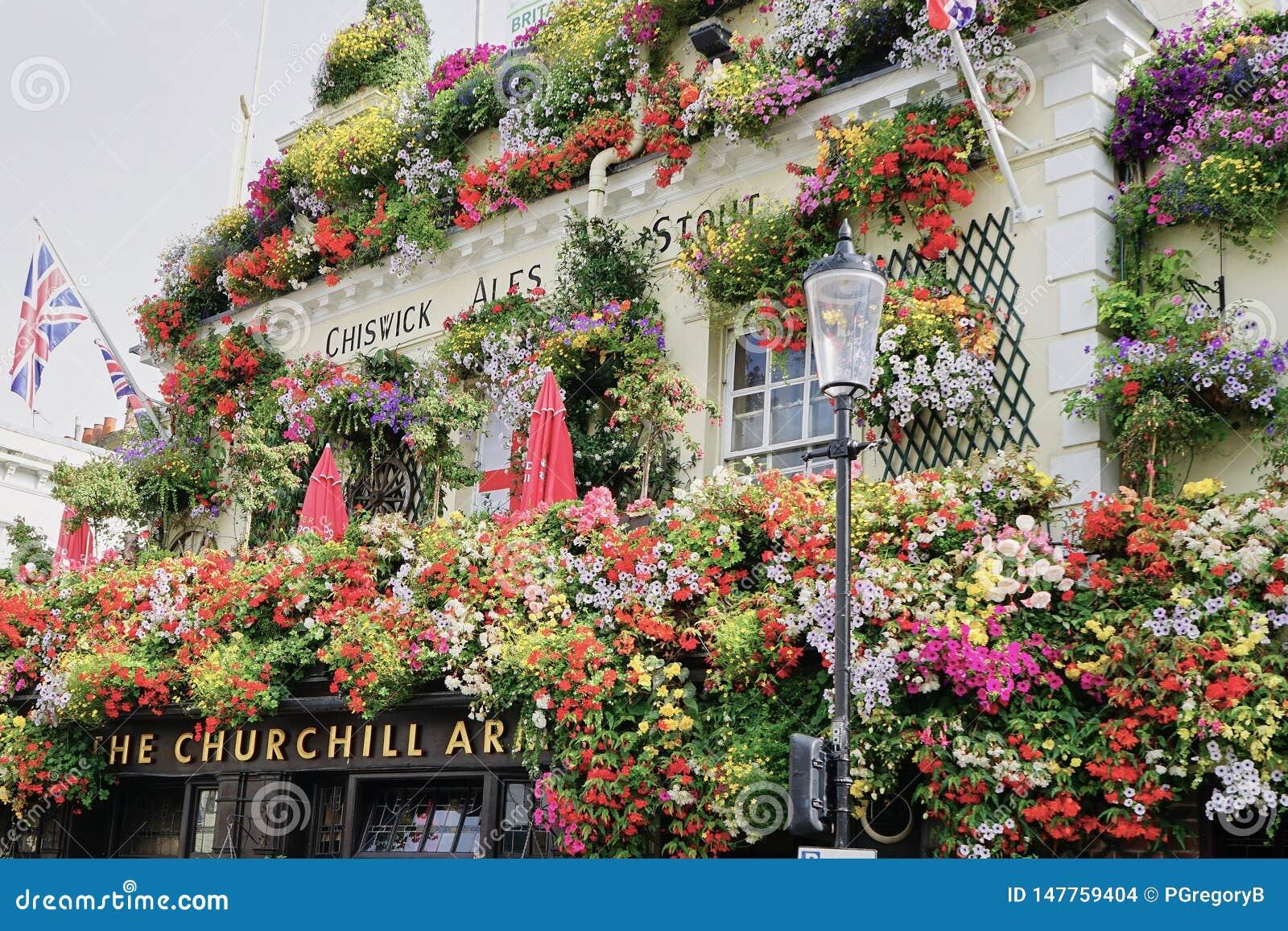 Неимоверный дисплей цветка на экстерьере паба руки Черчилль в Лондоне