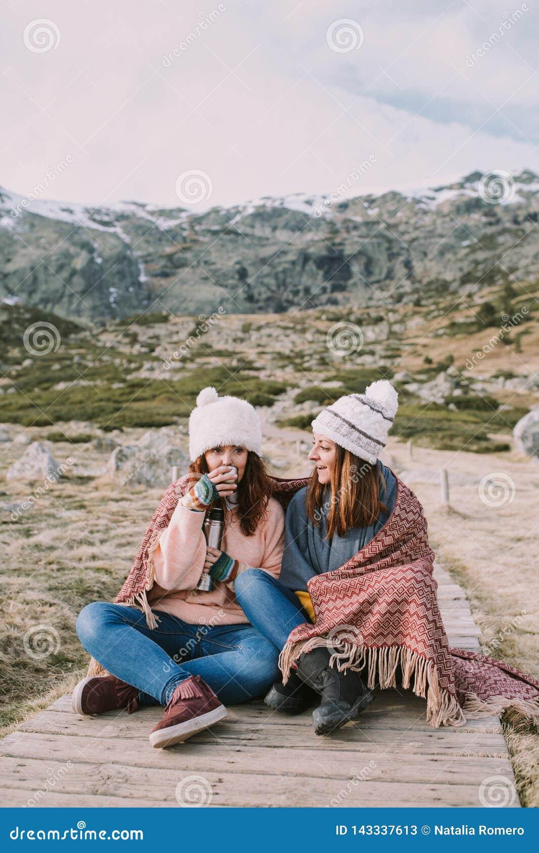 Некоторые друзья наслаждаются горой пока они сидят принимающ отвар