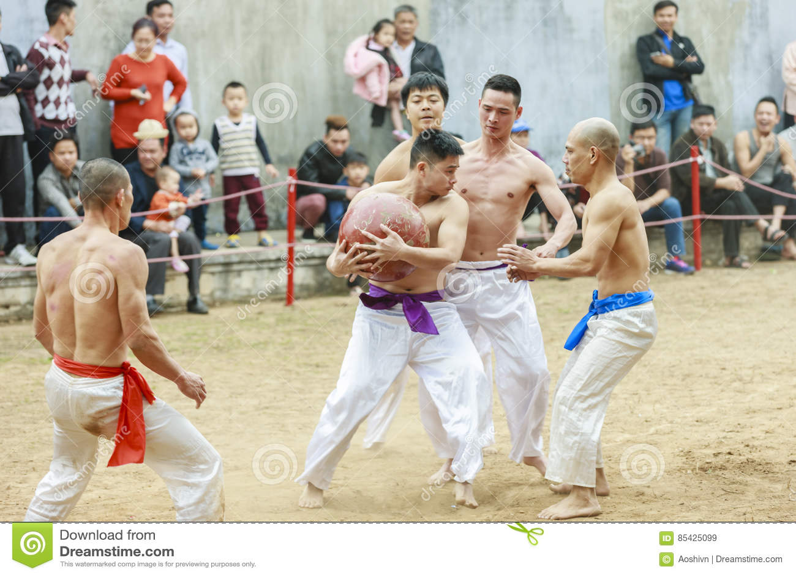 Некоторые молодые человеки играют с деревянным шариком в Новом Годе фестиваля лунном на Ханое, Вьетнаме 27-ого января 2016