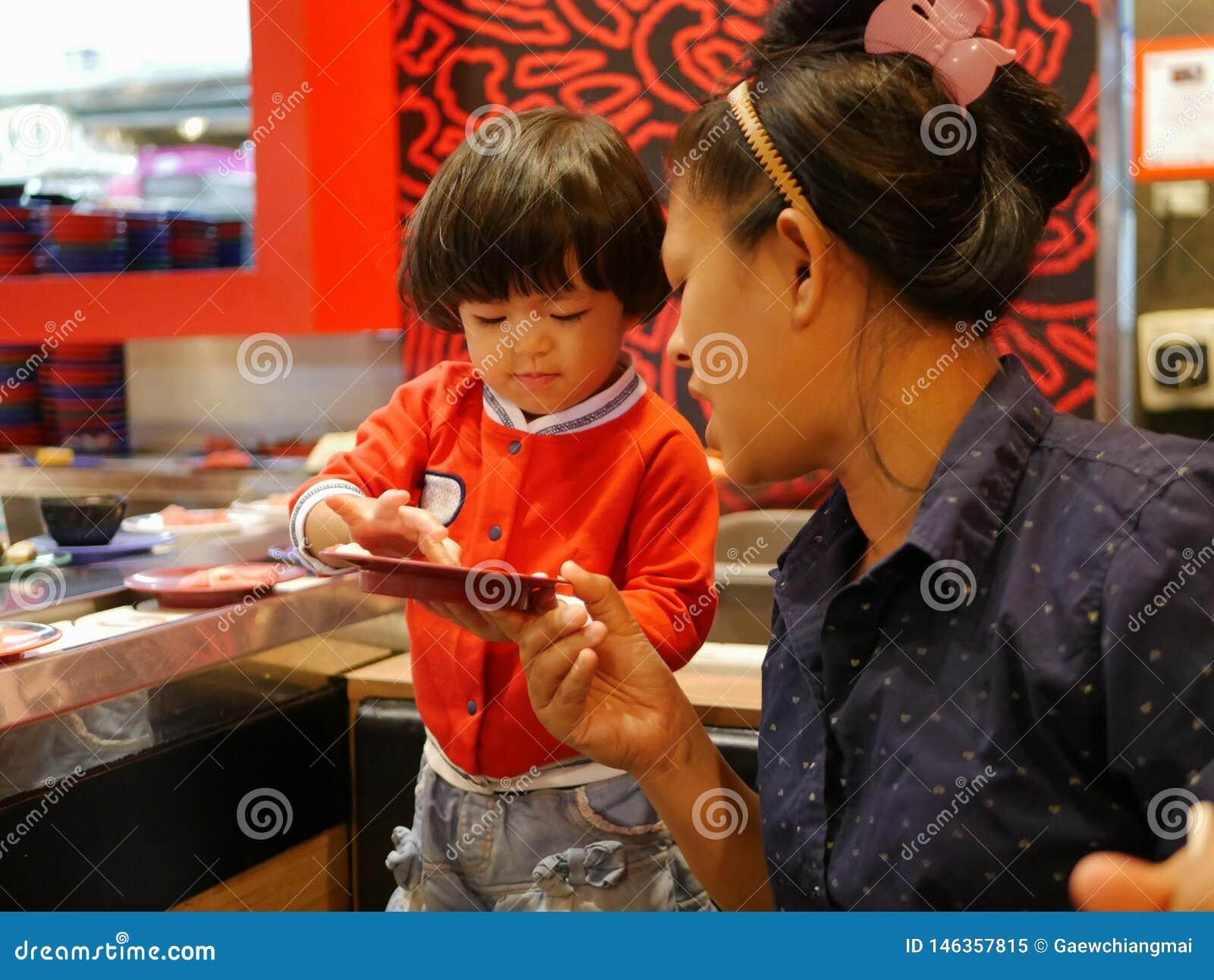 Немногое азиатский ребенок наслаждается скомплектовать сырцовые ингредиенты, для ее матери, для hotpot варя, служа на двигая конв