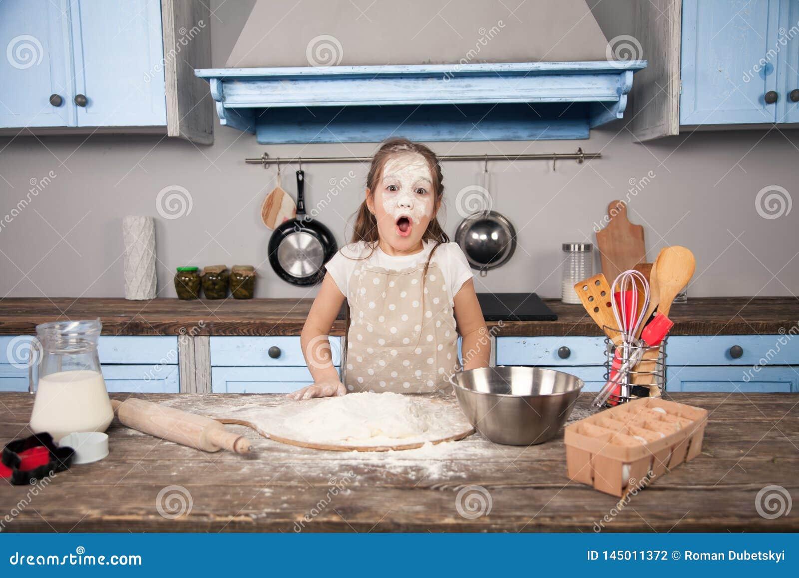 Немногое девушка дочери ребенка помогает ее матери в кухне сделать пе