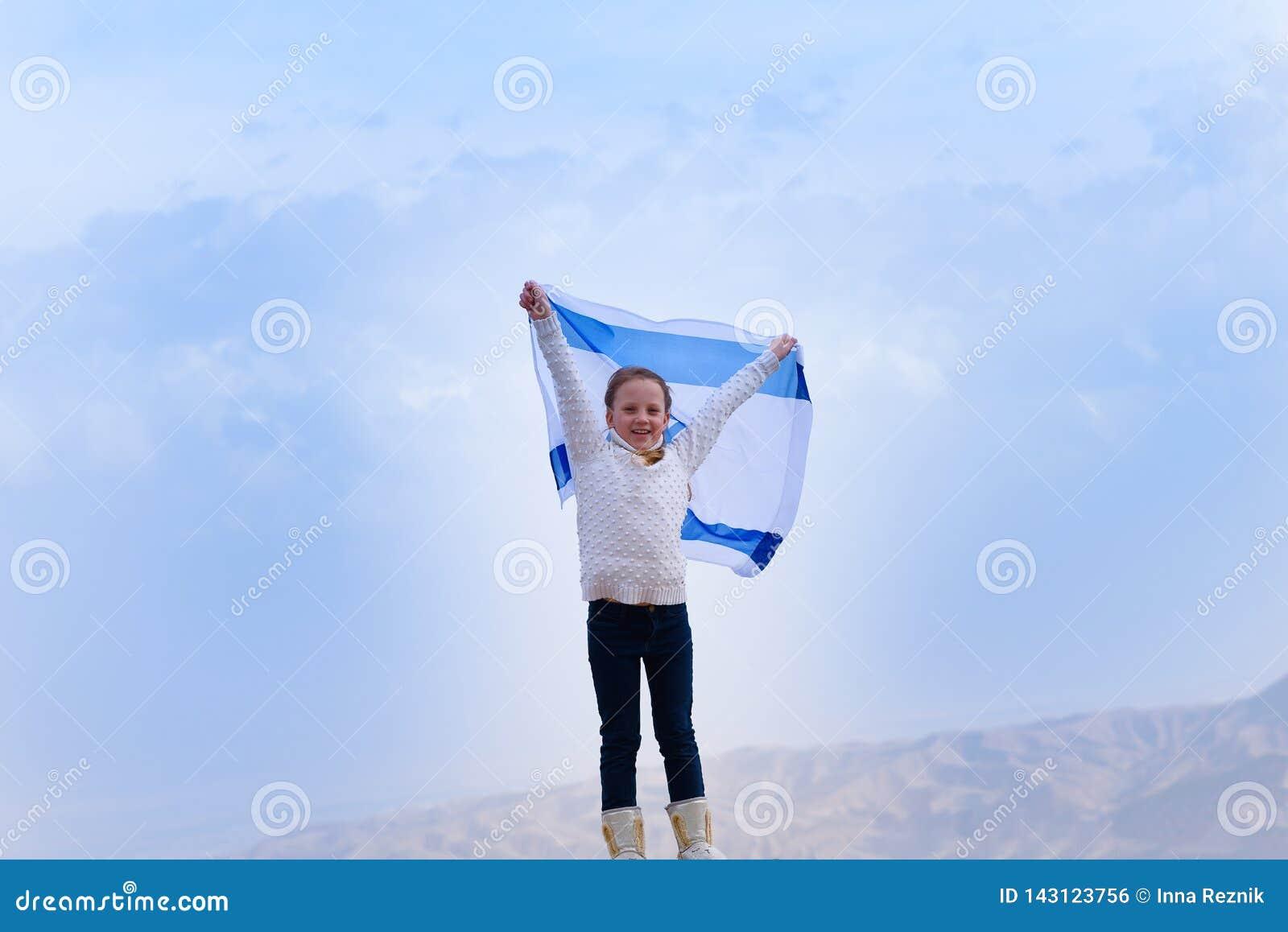 Немногое девушка патриота еврейская с флагом Израиля на предпосылке голубого неба