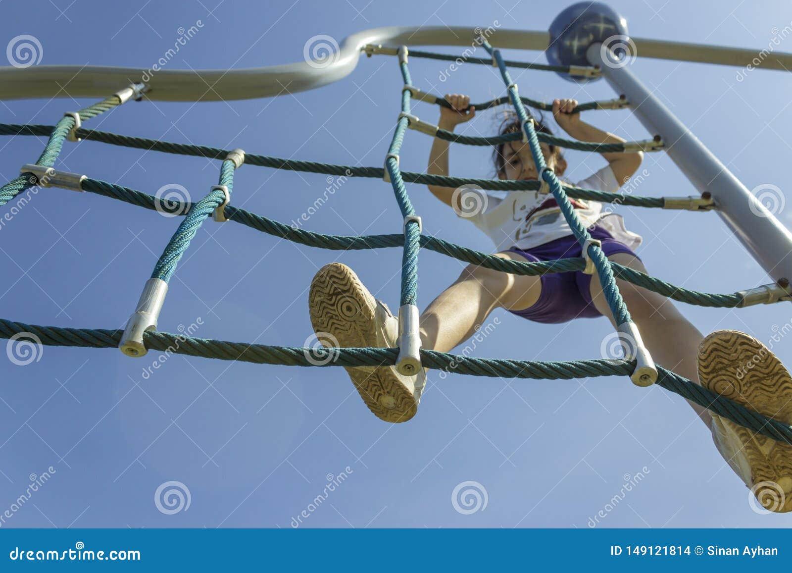 Немногое девушка школы beginner играя на спортивной площадке