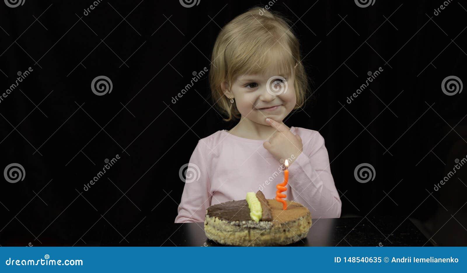 Немногое милая девушка делая желание перед свечой дуновения вне праздничной на именнином пироге