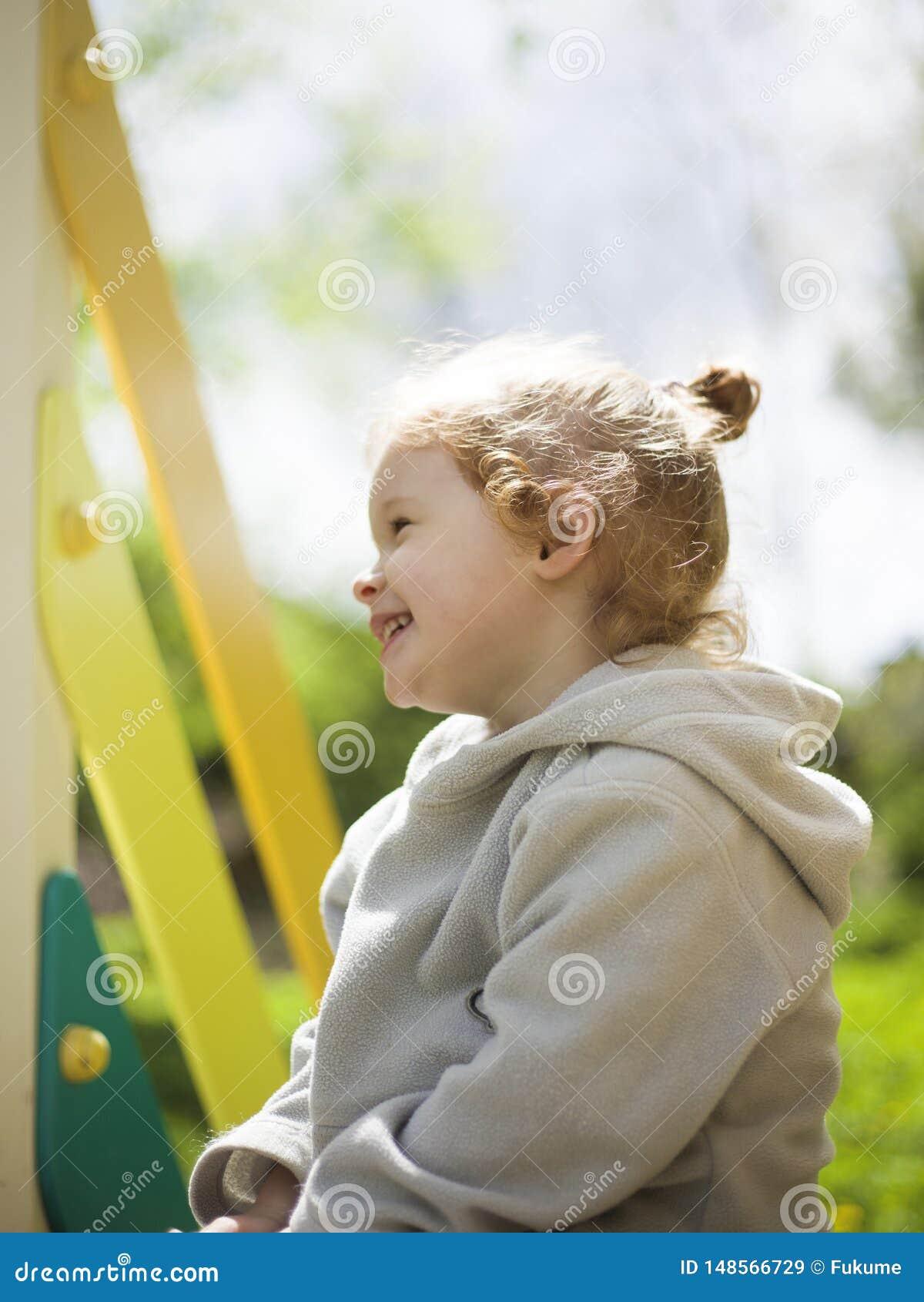 Немногое милая девушка сидит на дети сползает и греется в теплом солнце лета
