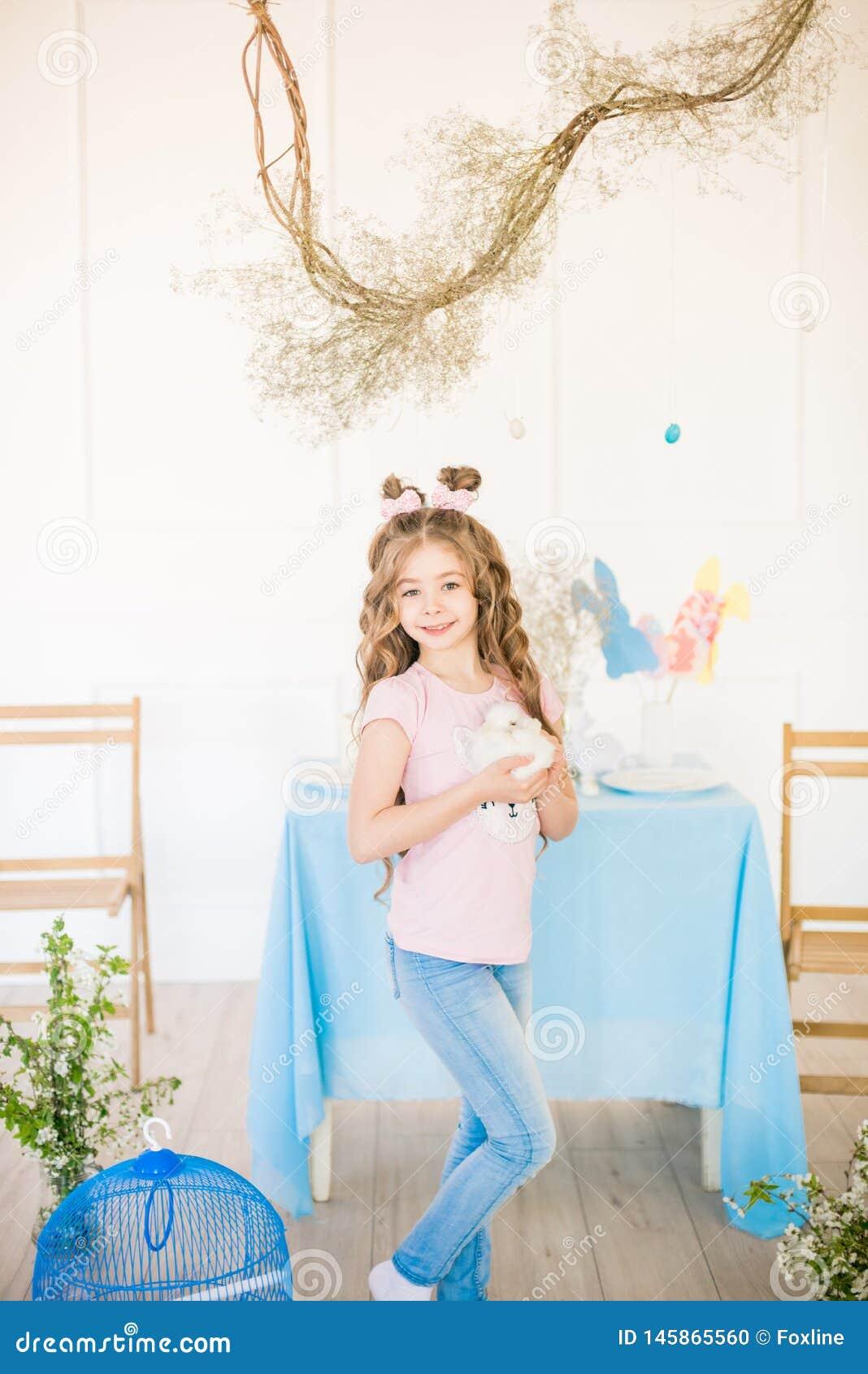 Немногое милая девушка с длинным вьющиеся волосы с маленькими зайчиками и оформлением пасхи дома на таблице