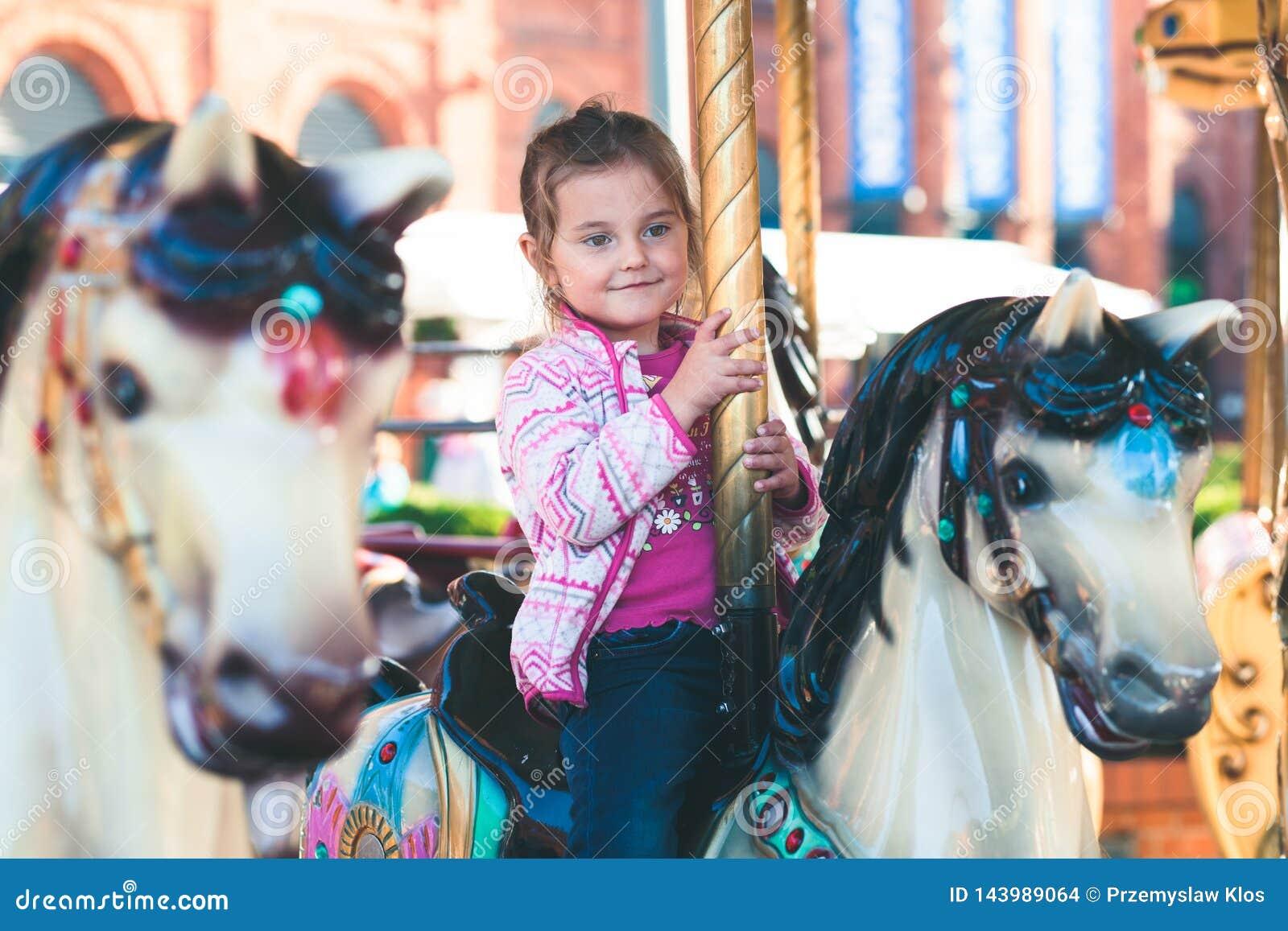 Немногое прелестная усмехаясь девушка ехать лошадь на carousel карусели на ярмарке