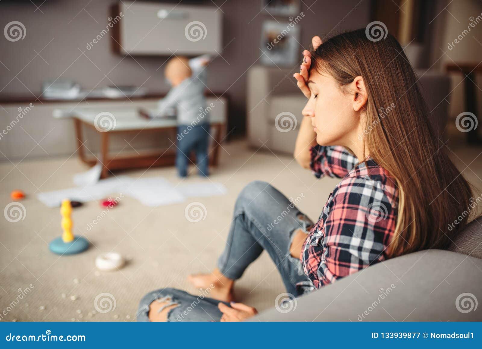 Немногое ребенок играя в комнате, мать в стрессе