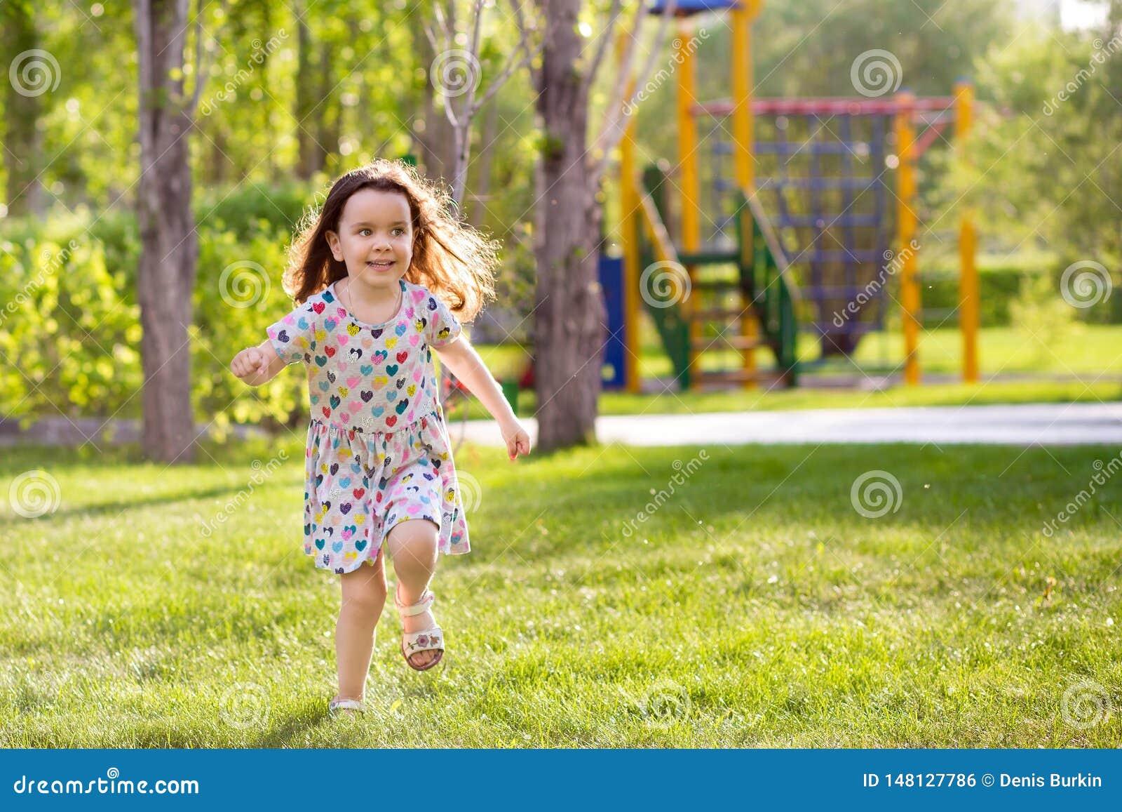 Немногое счастливые девушки на прогулке на вечере лета на заходе солнца в парке Сестры