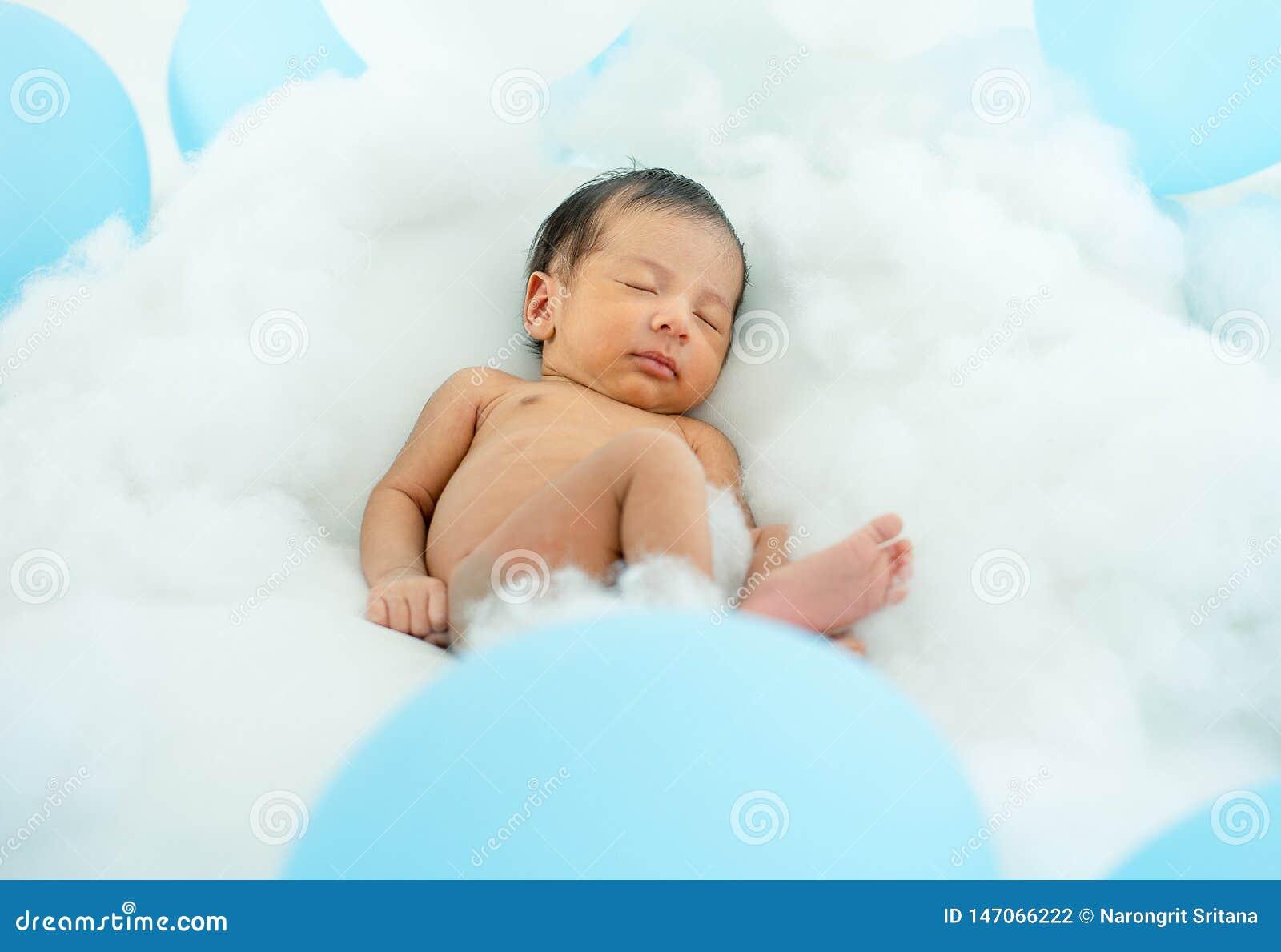 Немногое newborn младенец на пушистом панд с серией белого и голубого воздушного шара вокруг младенца