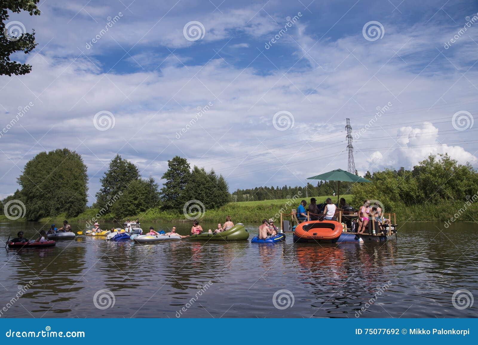 Неопознанные люди чертя вниз с реки на Kaljakellunta ( Пиво Floating) фестиваль