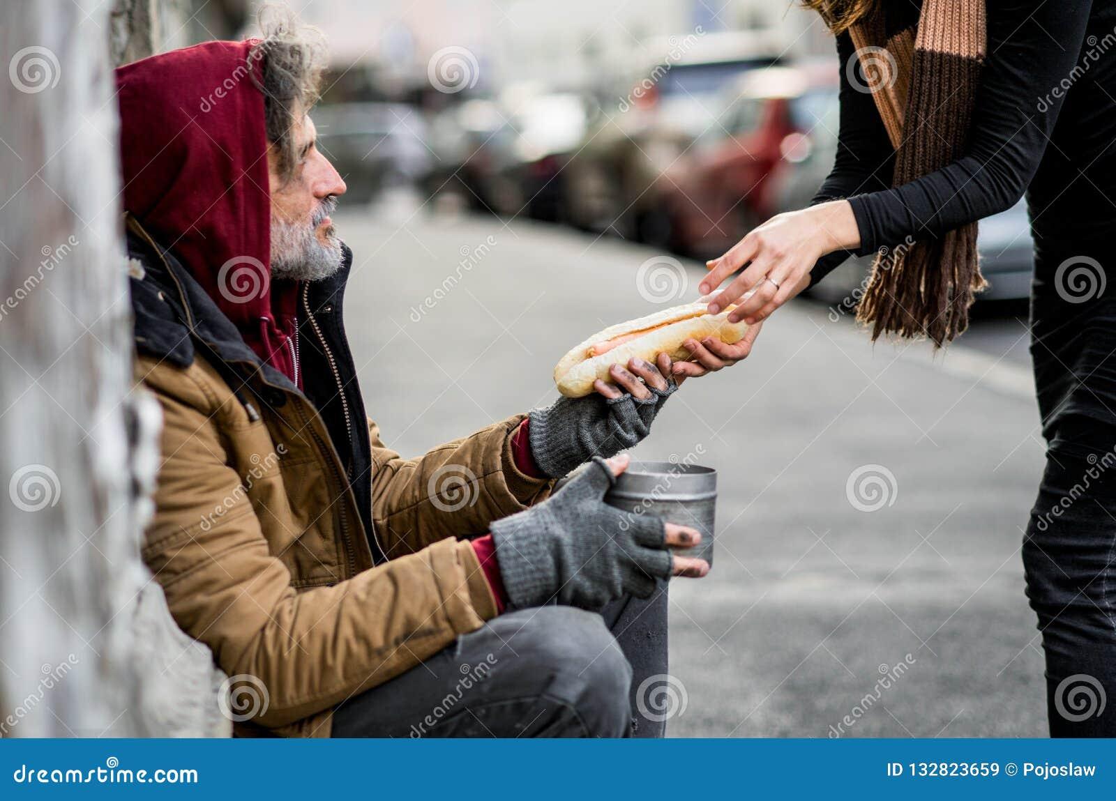 Непознаваемая женщина давая еду бездомному человеку попрошайки сидя в городе