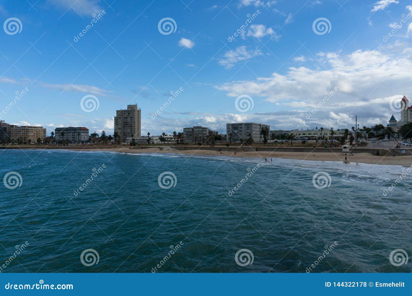 Непознаваемые люди ослабляя на пляже на Port Elizabeth, Южной Африке
