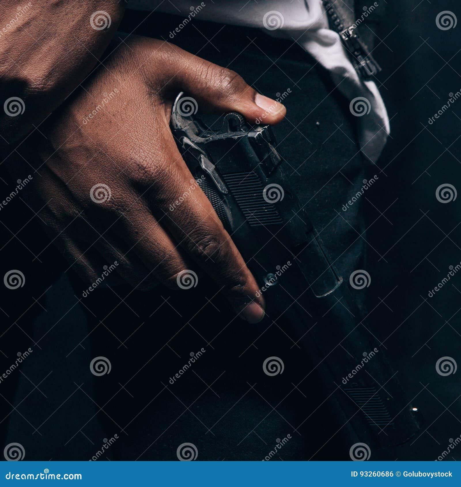 Непознаваемый вооруженный черный уголовный крупный план человека