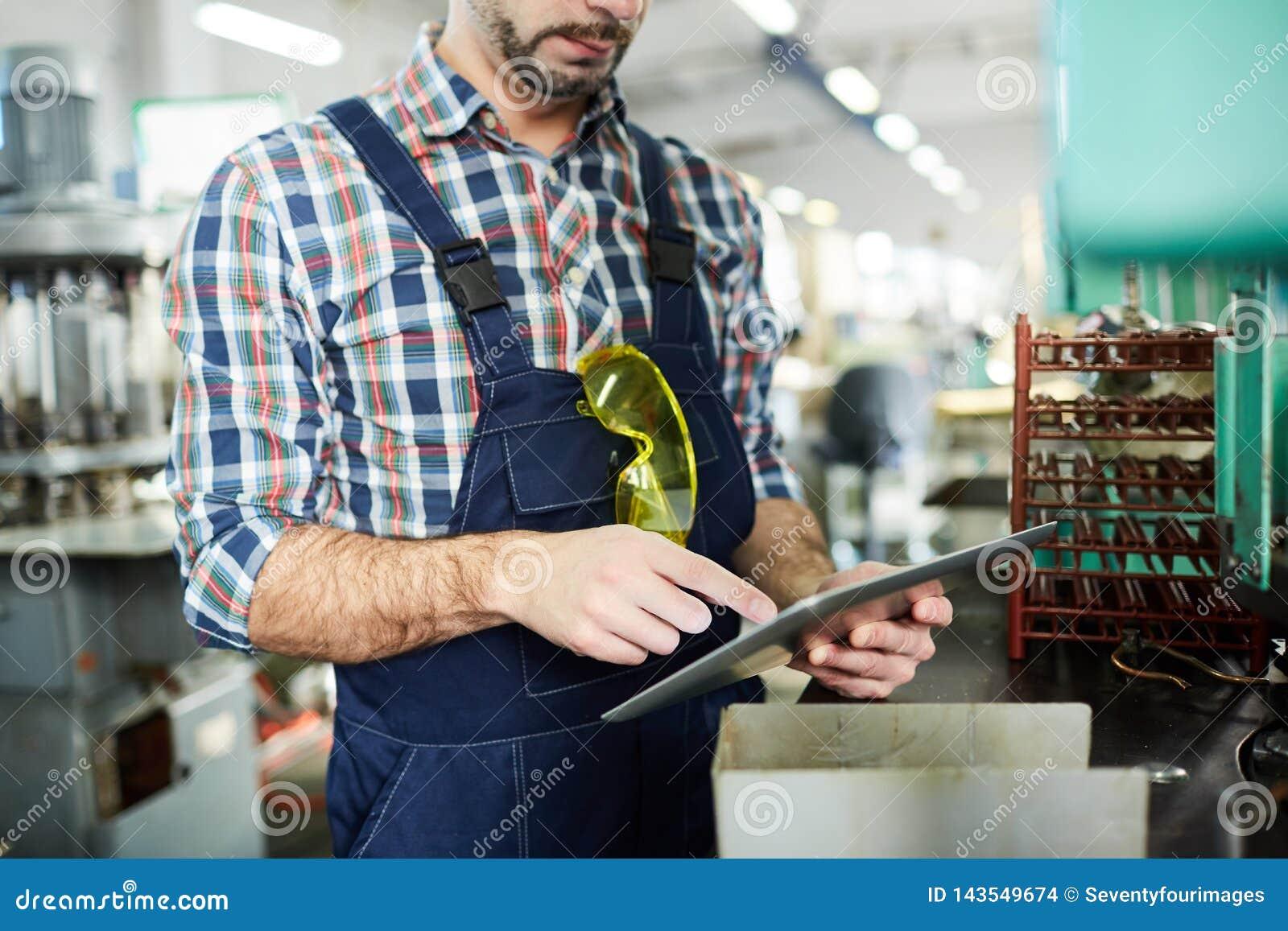 Непознаваемый заводской рабочий используя планшет