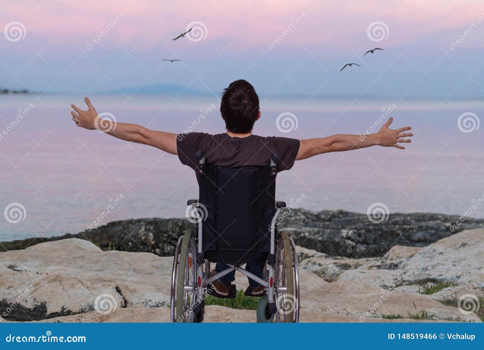 Неработающий человек на кресло-коляске около пляжа на заходе солнца