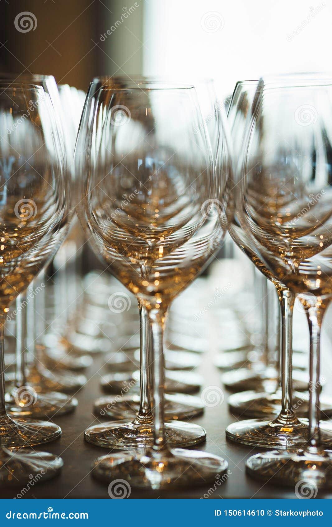 Несколько строк ясно, чистых стекла для вина и шампанское на счетчике подготовленном для напитков