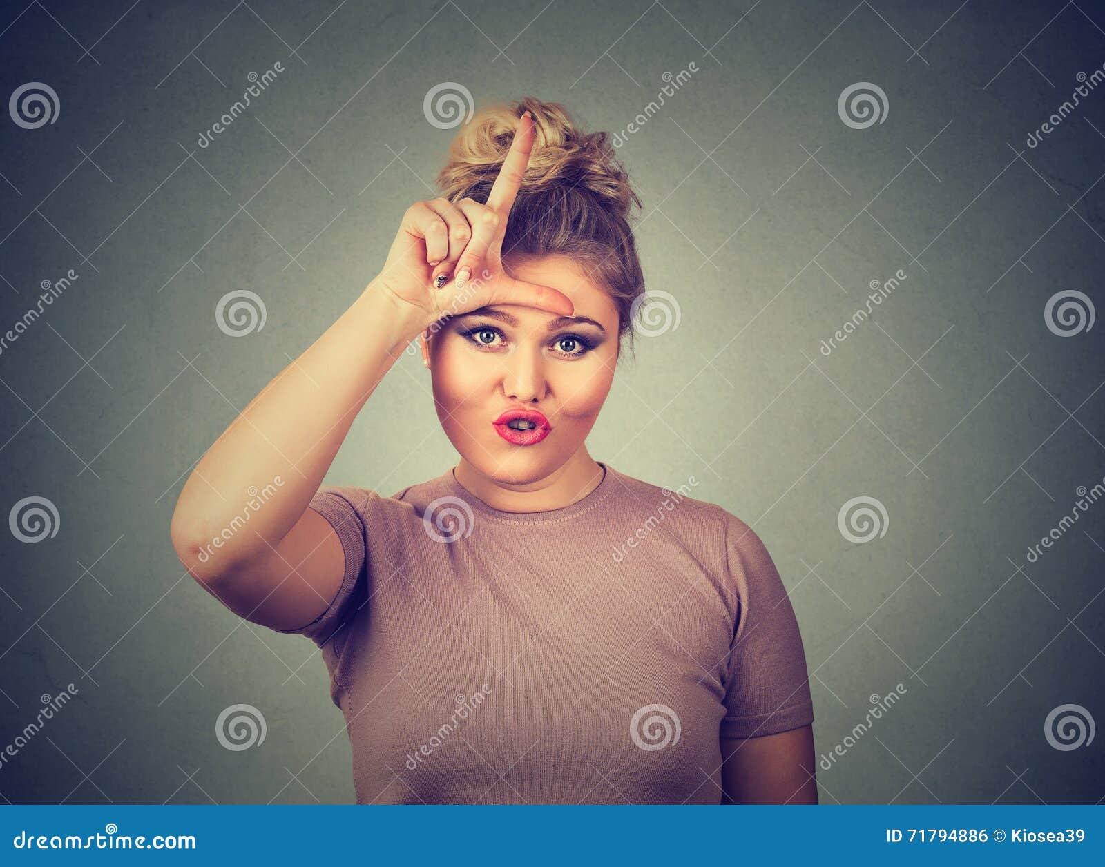 Несчастная женщина давая знак проигравшего на лбе, смотря вас, отвращение на стороне