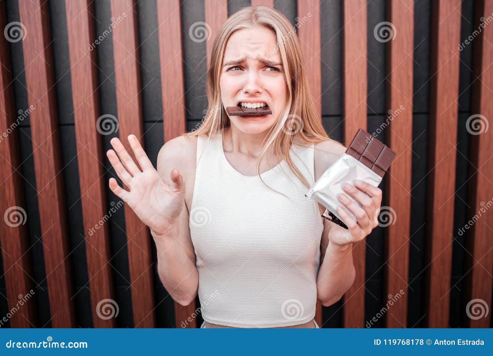 Несчастная молодая женщина держит шоколадный батончик в руке и ест большую часть в то же время Она чувствует виновной для