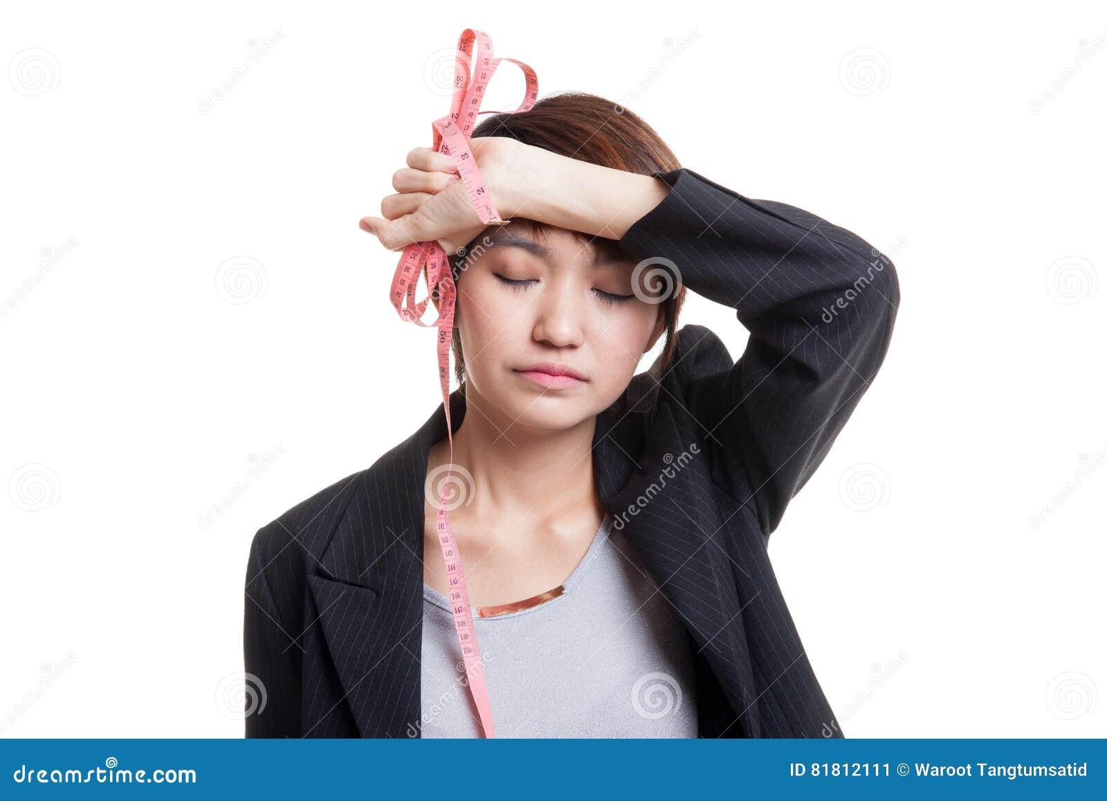 Несчастная молодая азиатская бизнес-леди с измеряя лентой