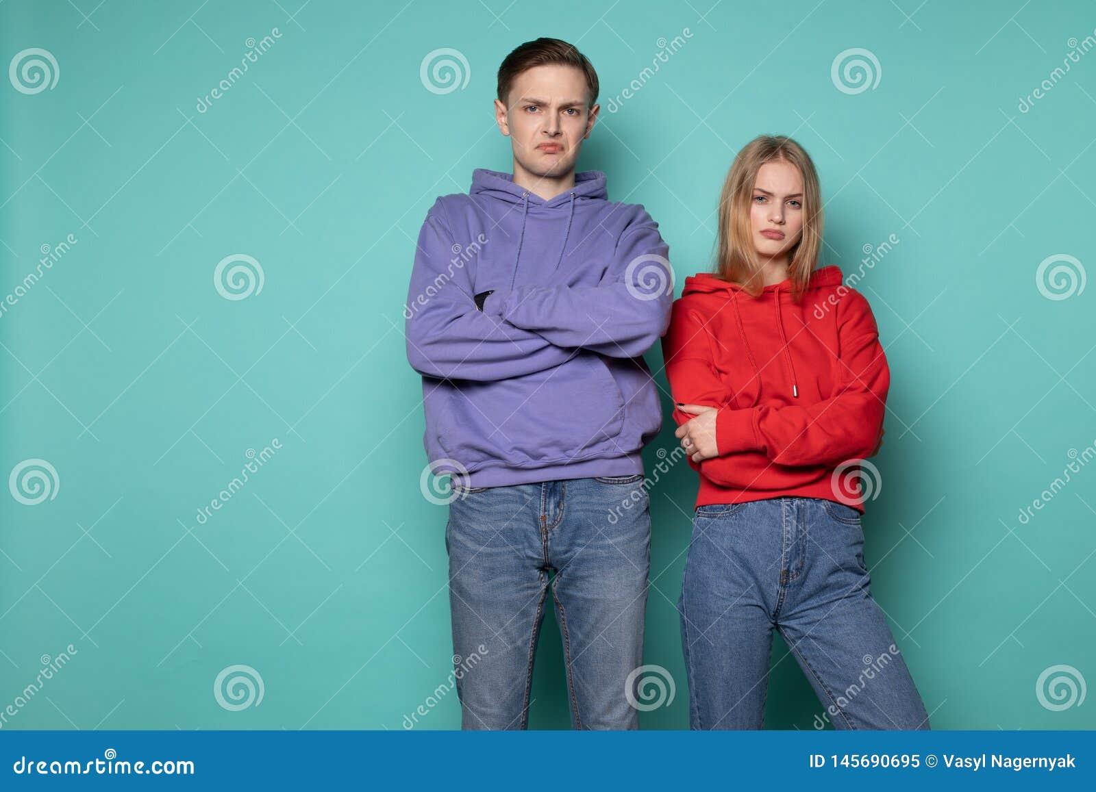 Несчастные сердитые человек и женщина людей в случайных одеждах, стоя совместно против голубой стены в студии