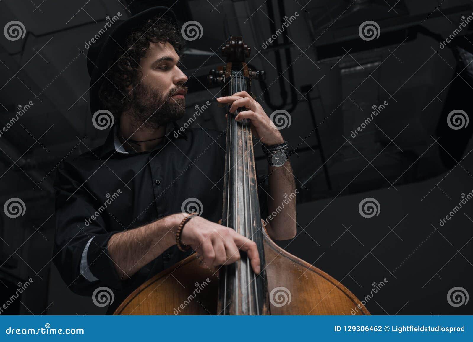 нижний взгляд молодого красивого музыканта