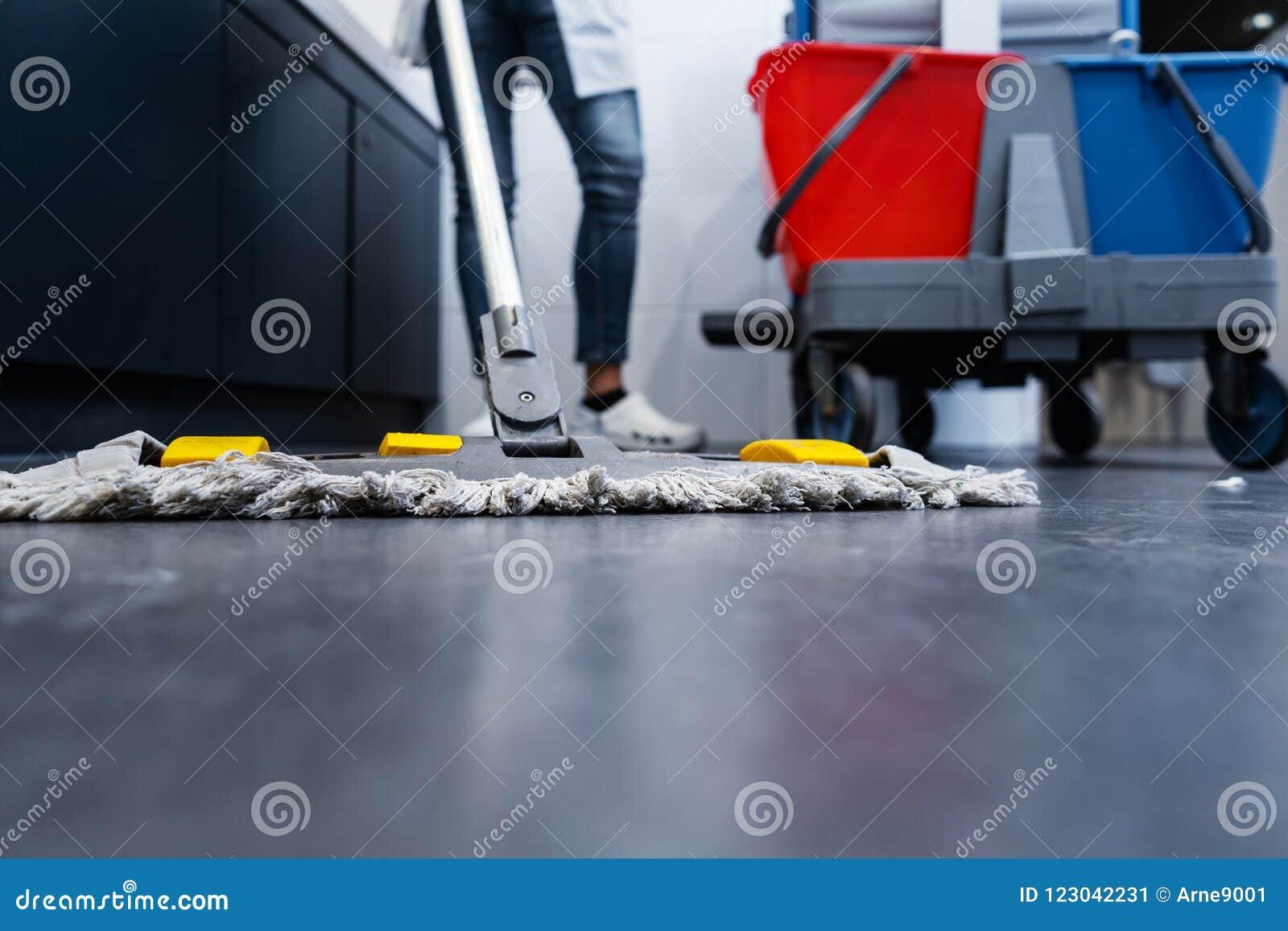 Низкая съемка уборщицы mopping пол в уборном