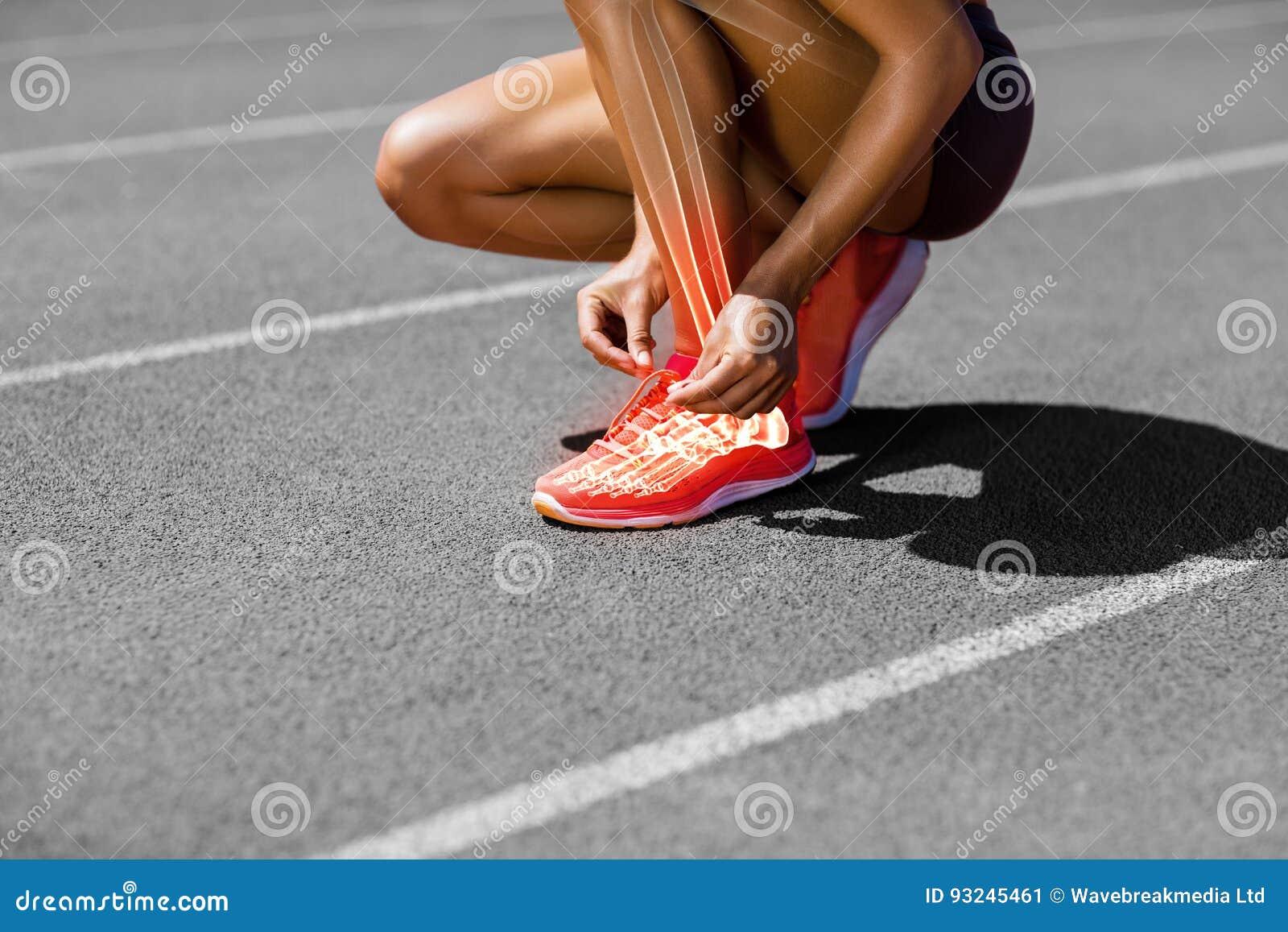 Низкий раздел спортсменки связывая шнурок на следе
