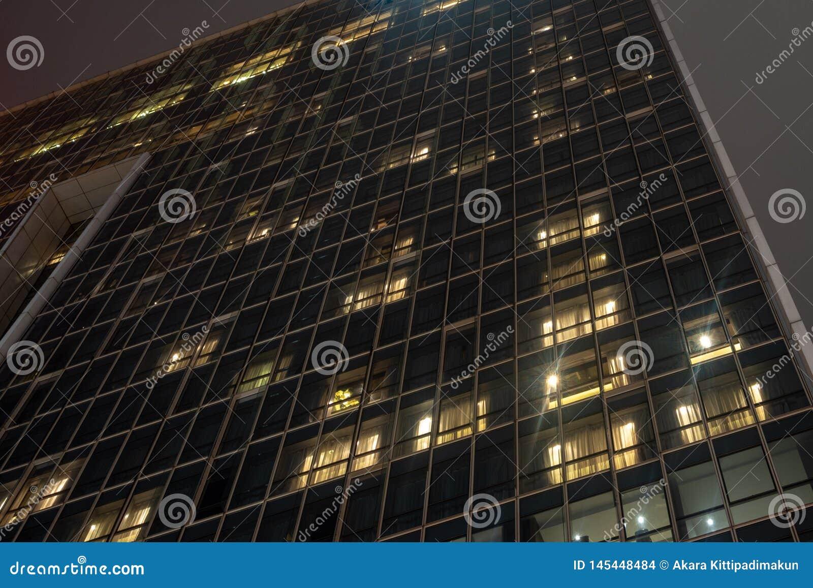 Низкий угол здания со стеклянным экстерьером на предпосылке ночного неба