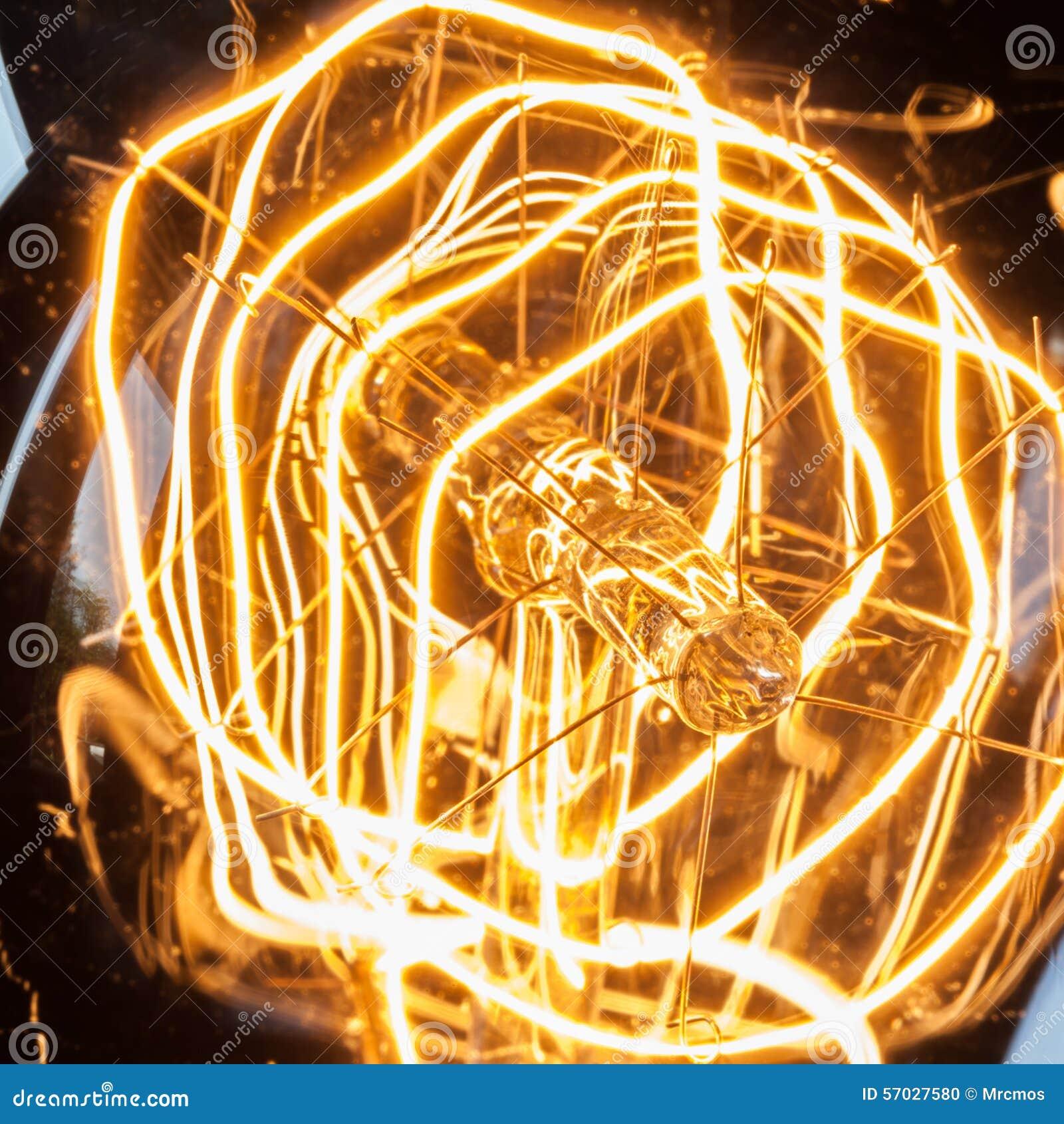 Нить крупного плана закрепляя петлей винтажной электрической лампочки edison