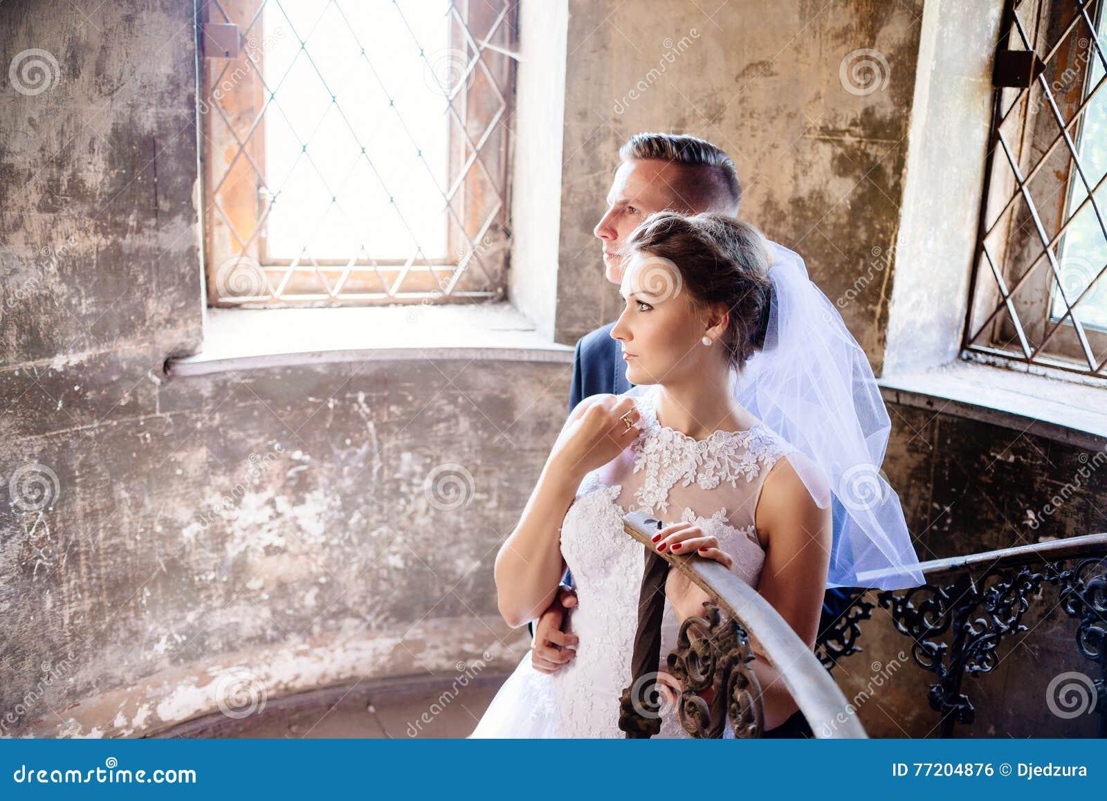 Новобрачные приближают к старым лестницам венчание сбора винограда дня пар одежды счастливое