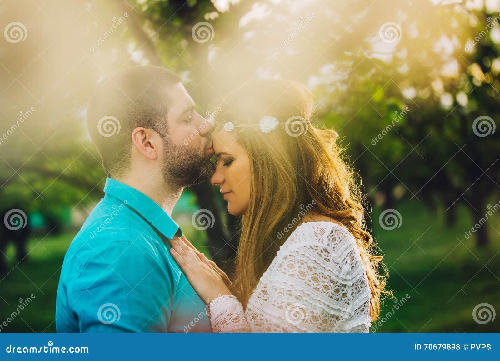 новые пожененные пары целуя в древесине вишни на заходе солнца