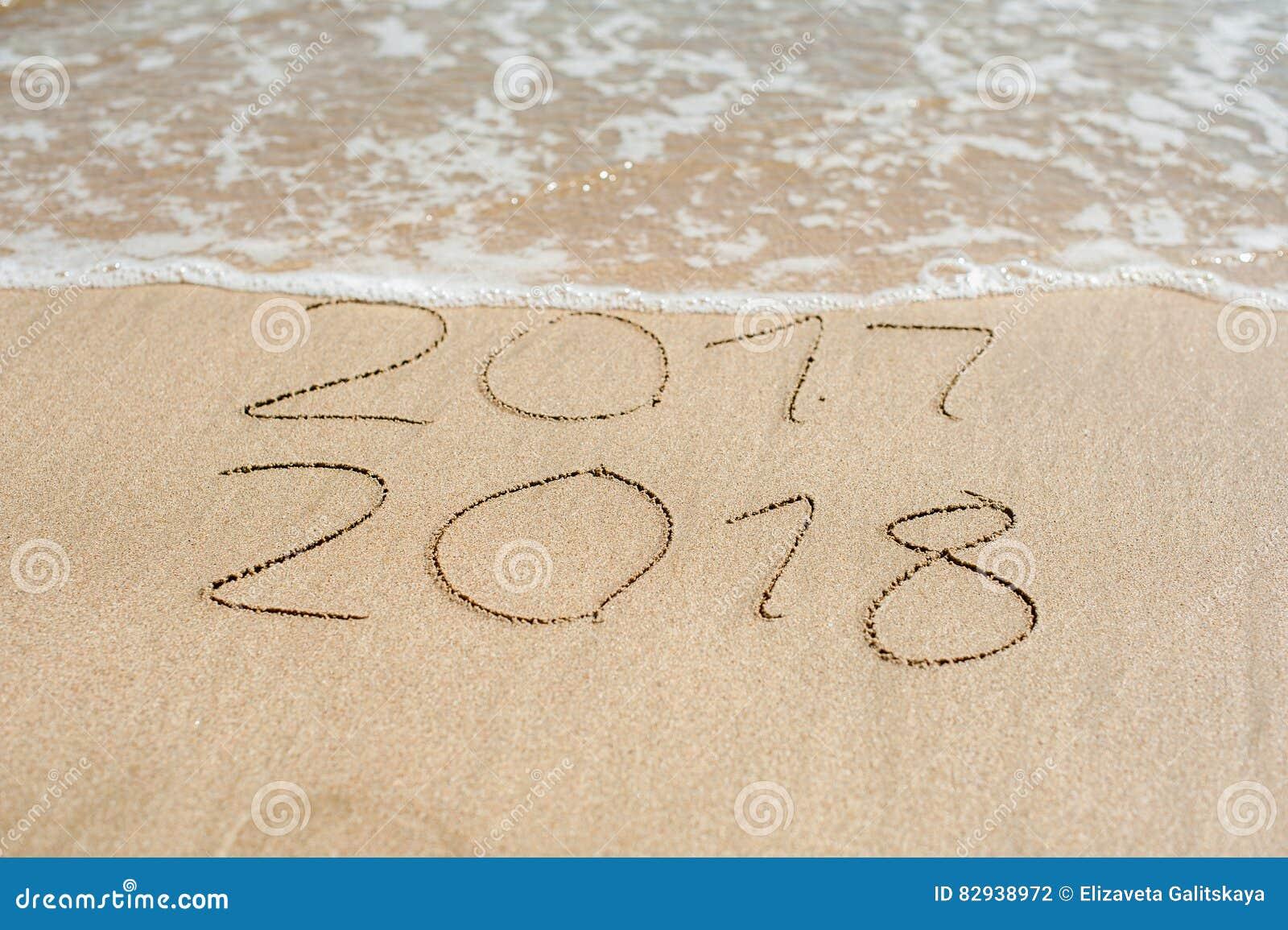 Новый Год 2018 приходя концепция - надпись 2017 и 2018 на песке пляжа, волна почти покрывает числа 2017
