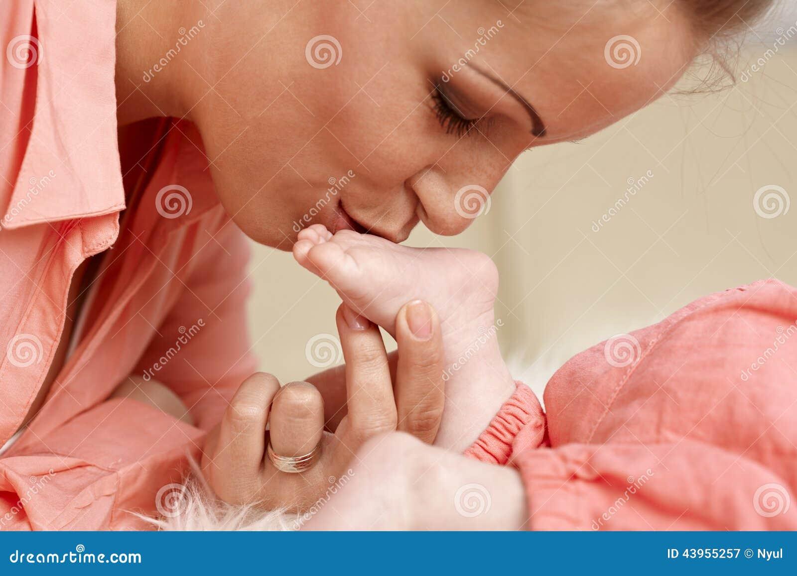 Нога младенца матери целуя сладостная