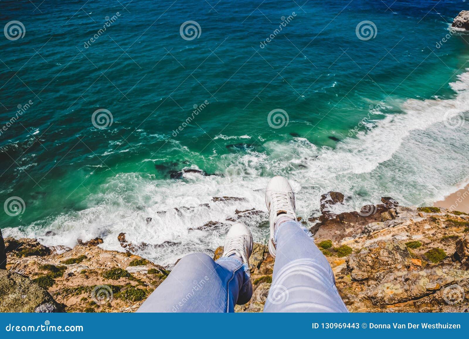 Ноги вися над краем скалы