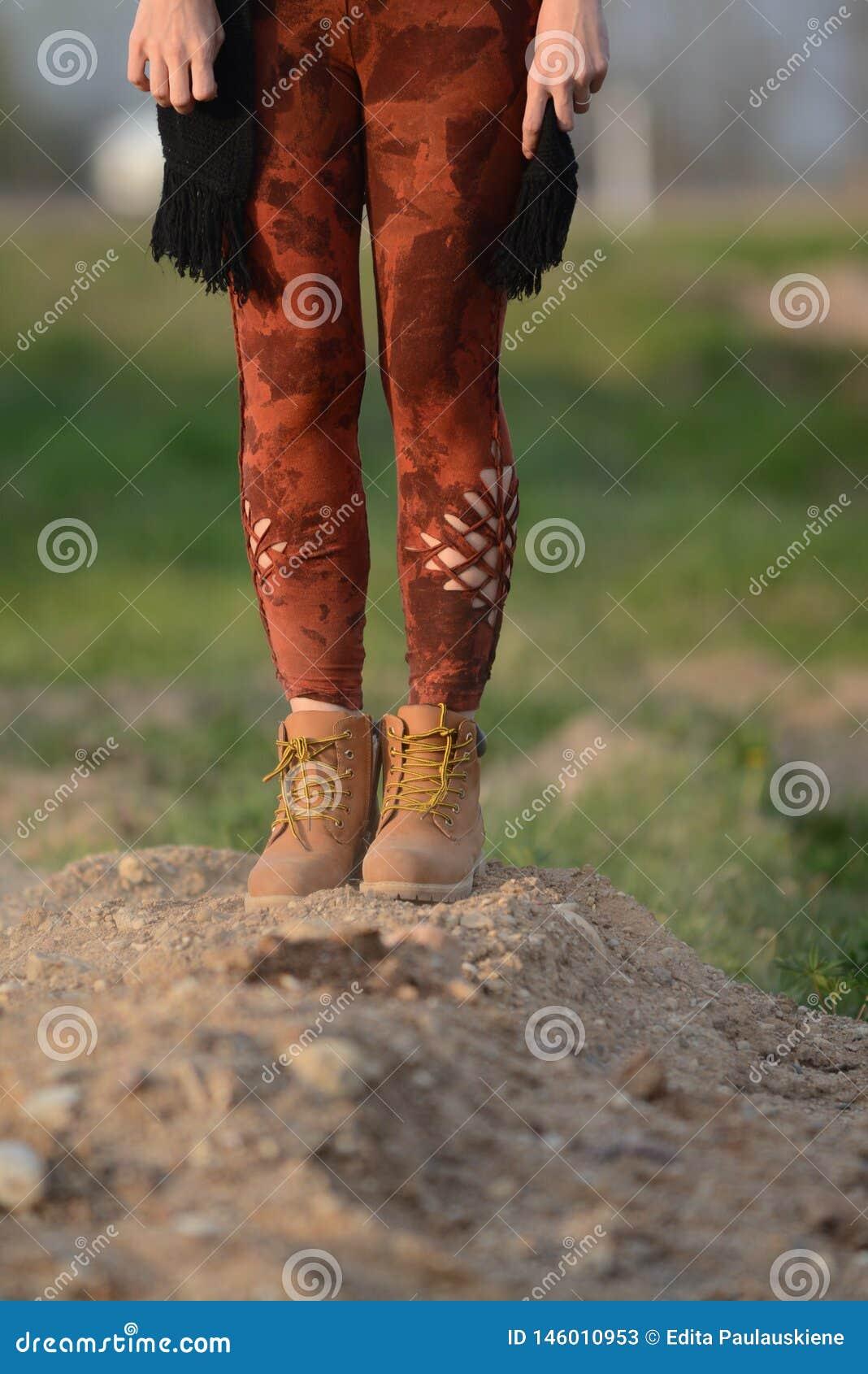 Ноги в красивых и уникальных отрезка колготках вне, моде фестиваля, золотом часе, теплом вечере