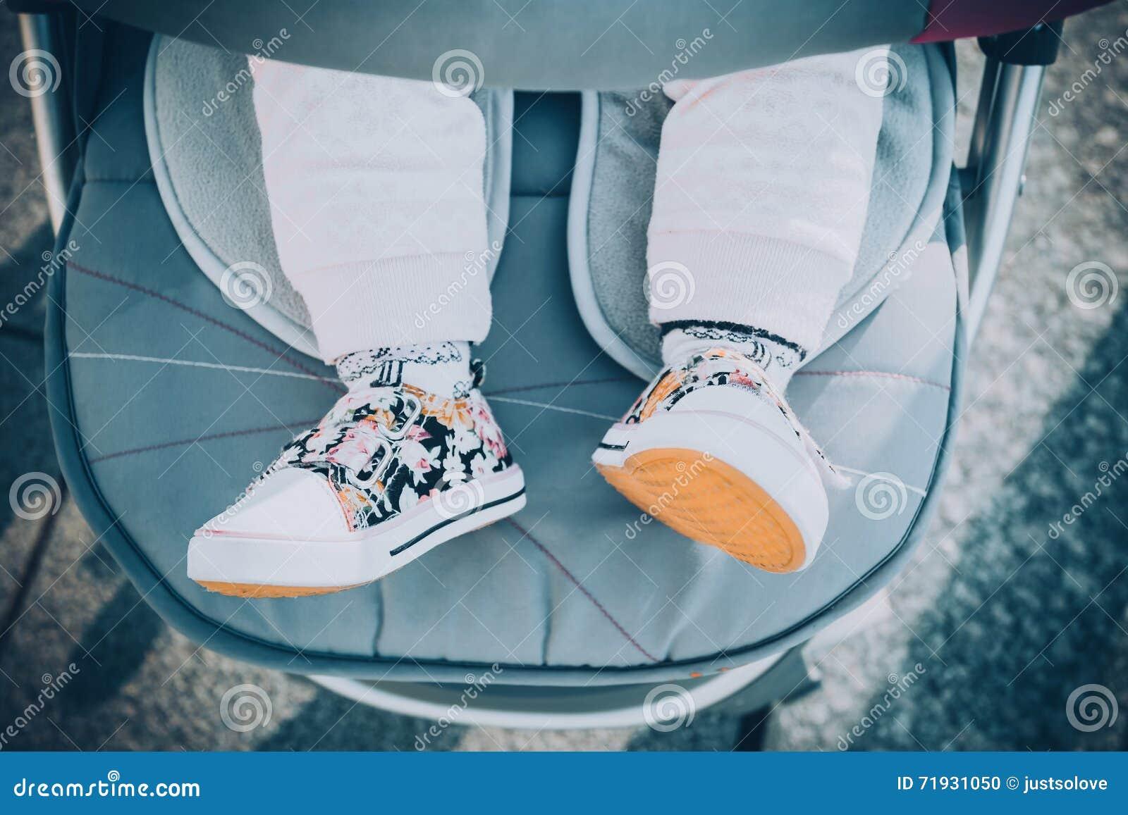 Ноги детей в детской дорожной коляске