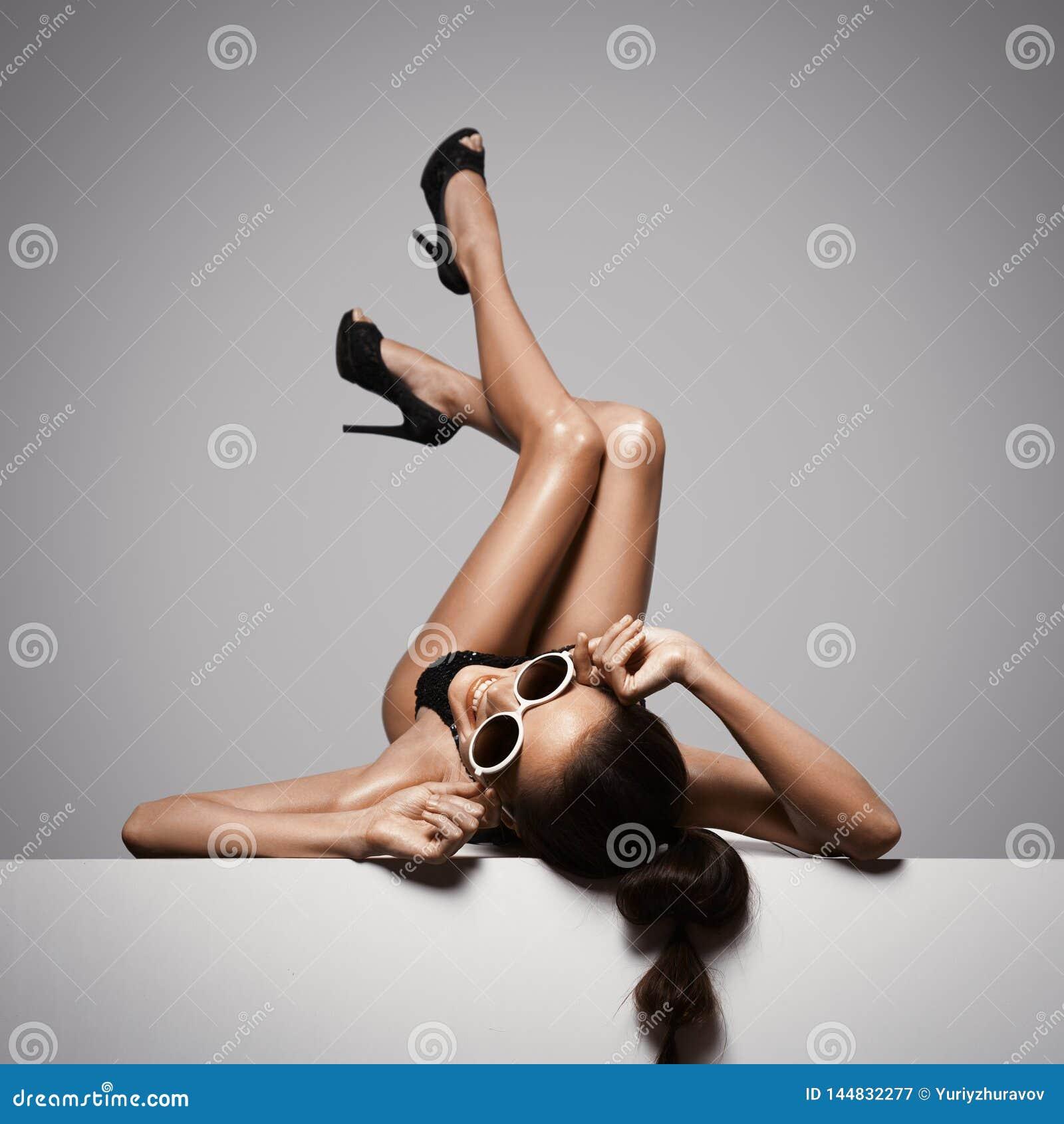 Ноги женщины сексуальные в черных ботинках Предпосылка серого цвета