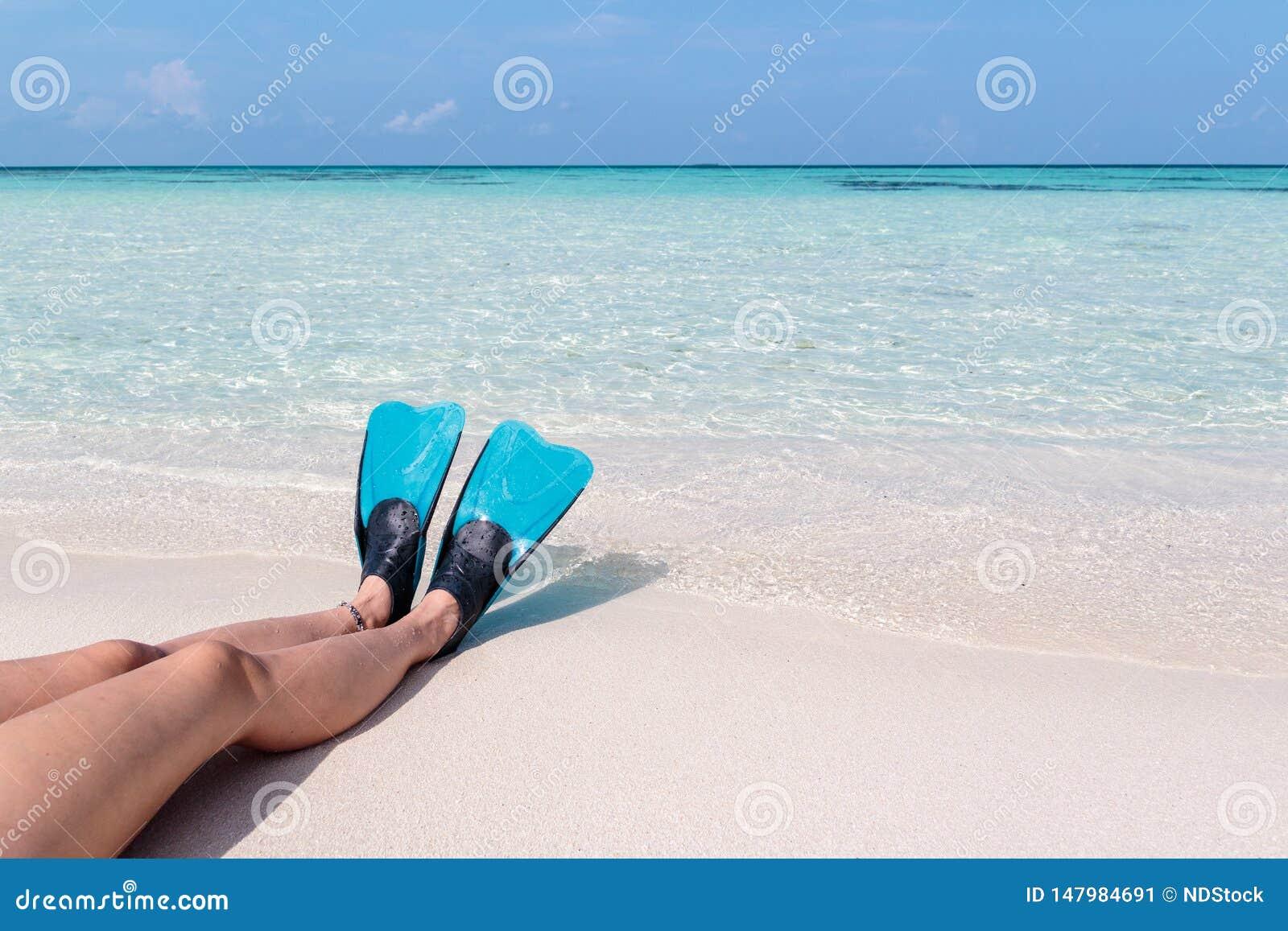 Ноги женщины с флипперами на белом пляже в Мальдивах Кристально ясное открытое море как предпосылка