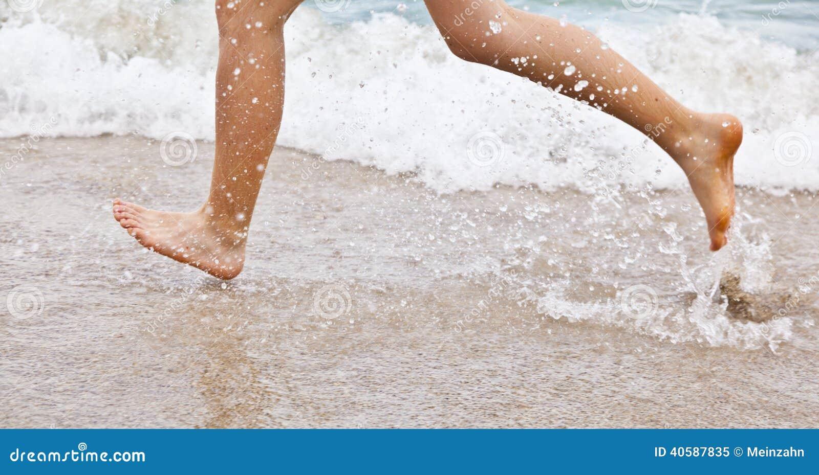 Ноги мальчика который бежит вдоль пляжа