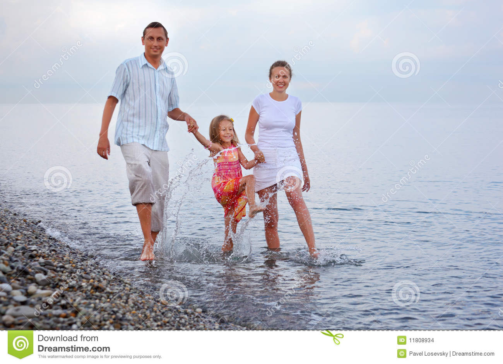 ноги семьи пляжа счастливые брызгают воду
