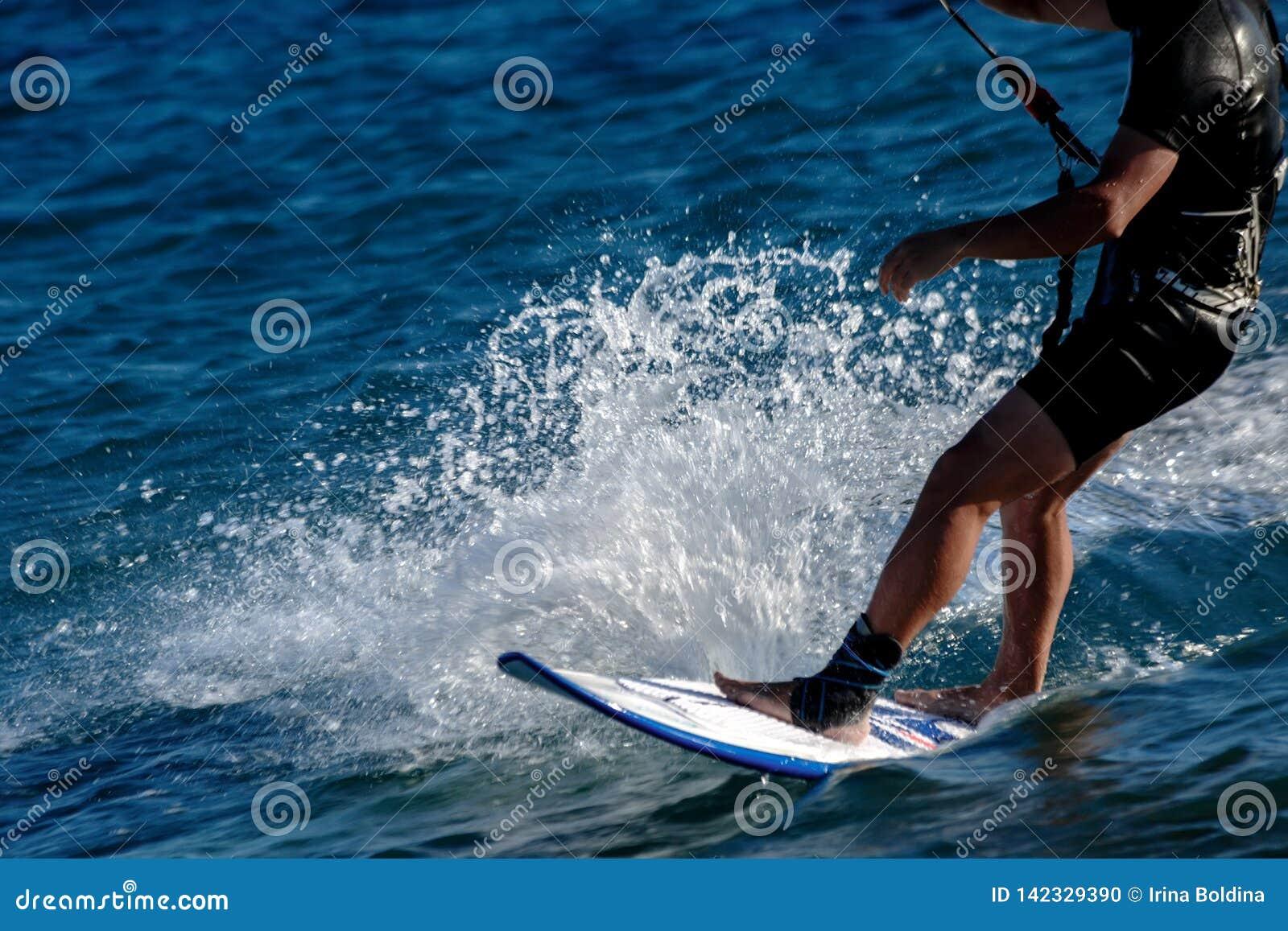 Ноги человека закрывают вверх на серфинге плавая доски